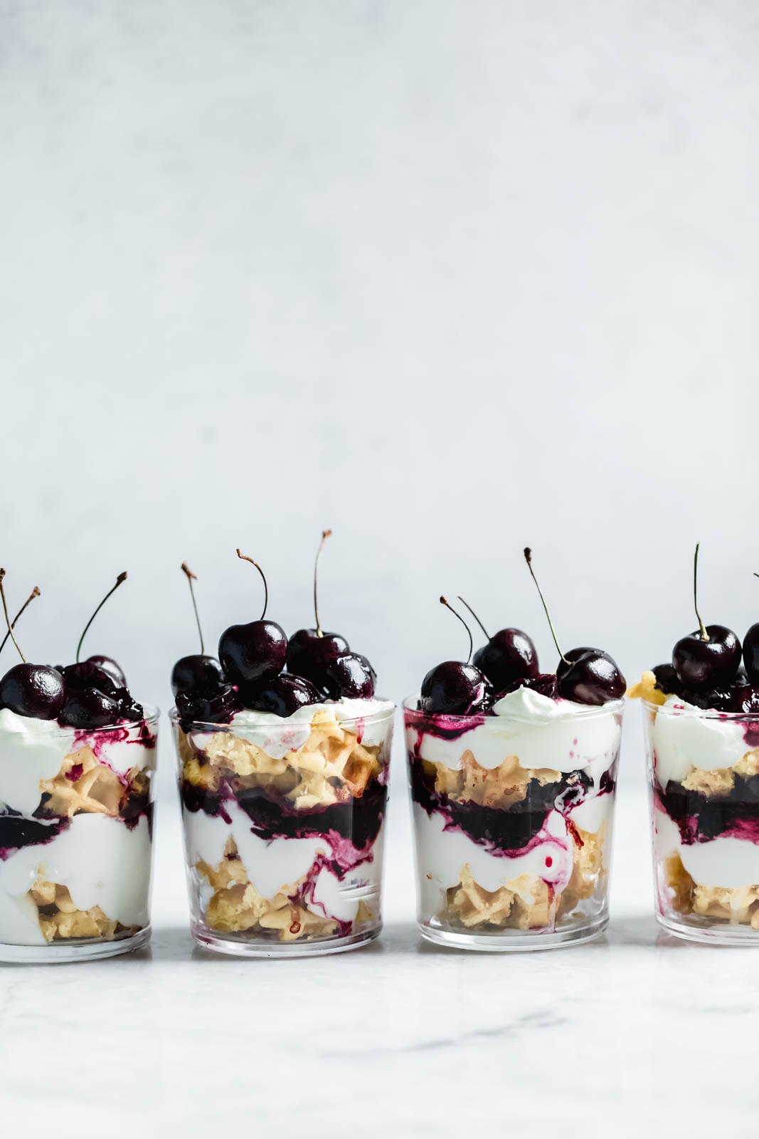 Layers of quick sautéed black cherries, fresh whipped cream, and Belgian waffles make this no-bake waffle parfait a total no-brainer summer dessert.