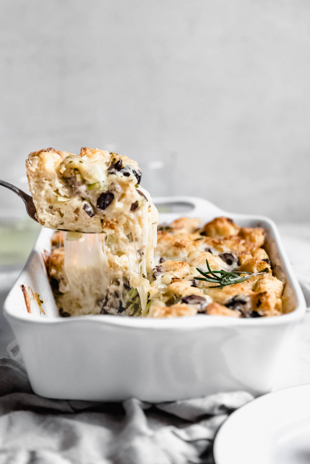 scooping out savory bread pudding from a casserole dish