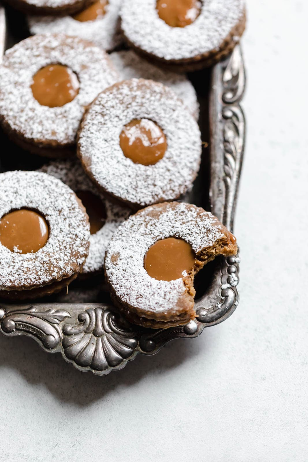 Gingerbread Linzer Cookies topped with powdered sugar
