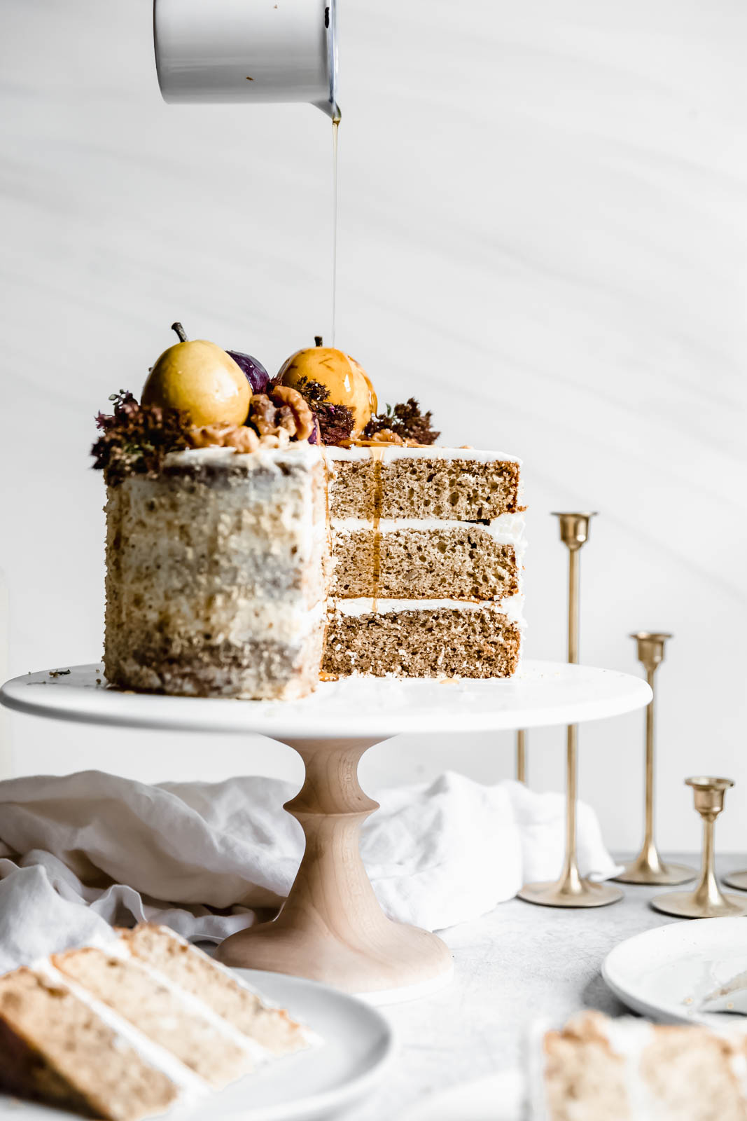 drizzling maple syrup on Maple Walnut Cake with Maple Frosting