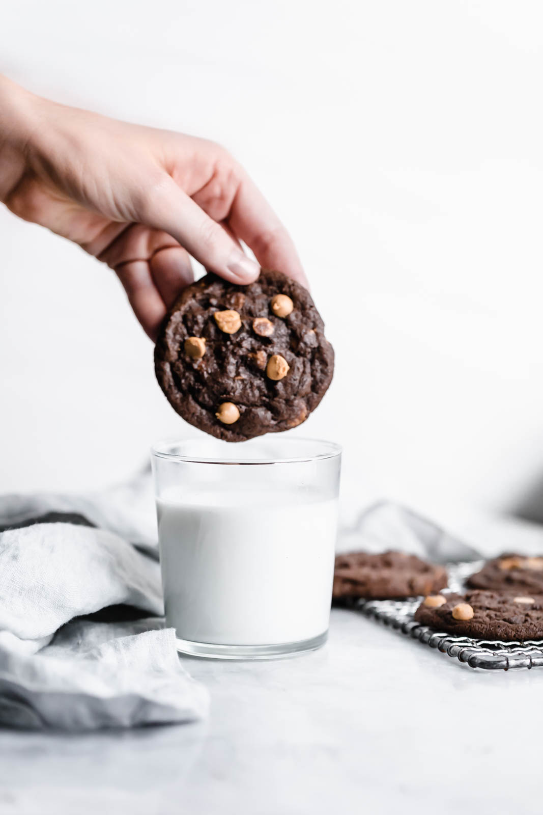 dunking Chocolate Peanut Butter Chip Cookie into glass of milk