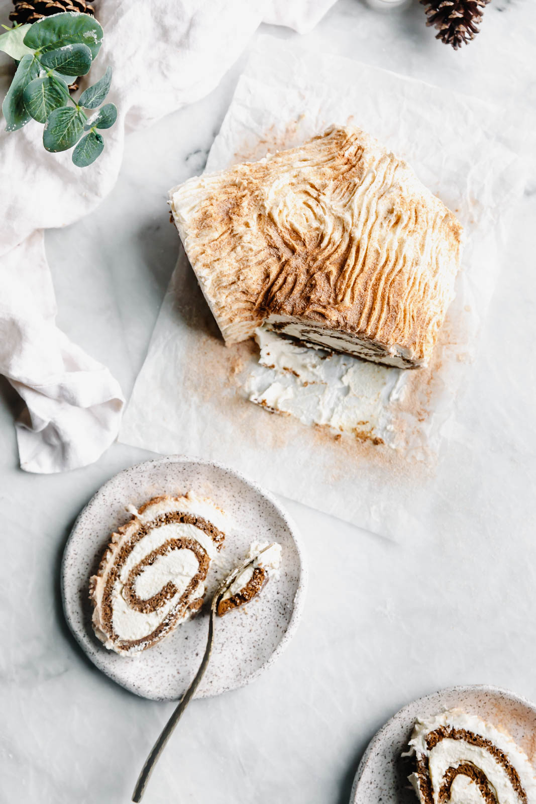 "This festive White Chocolate Gingerbread Yule Log is a showstopper Christmas dessert. Made with white chocolate buttercream ""bark"" for that rustic look!"