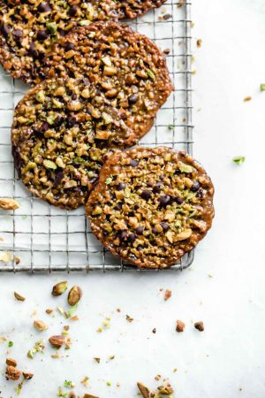These crunchy, nutty, chocolatey homemade lace cookies, put a spin on a classic with chopped pistachios and dark chocolate. Try to eat just one.