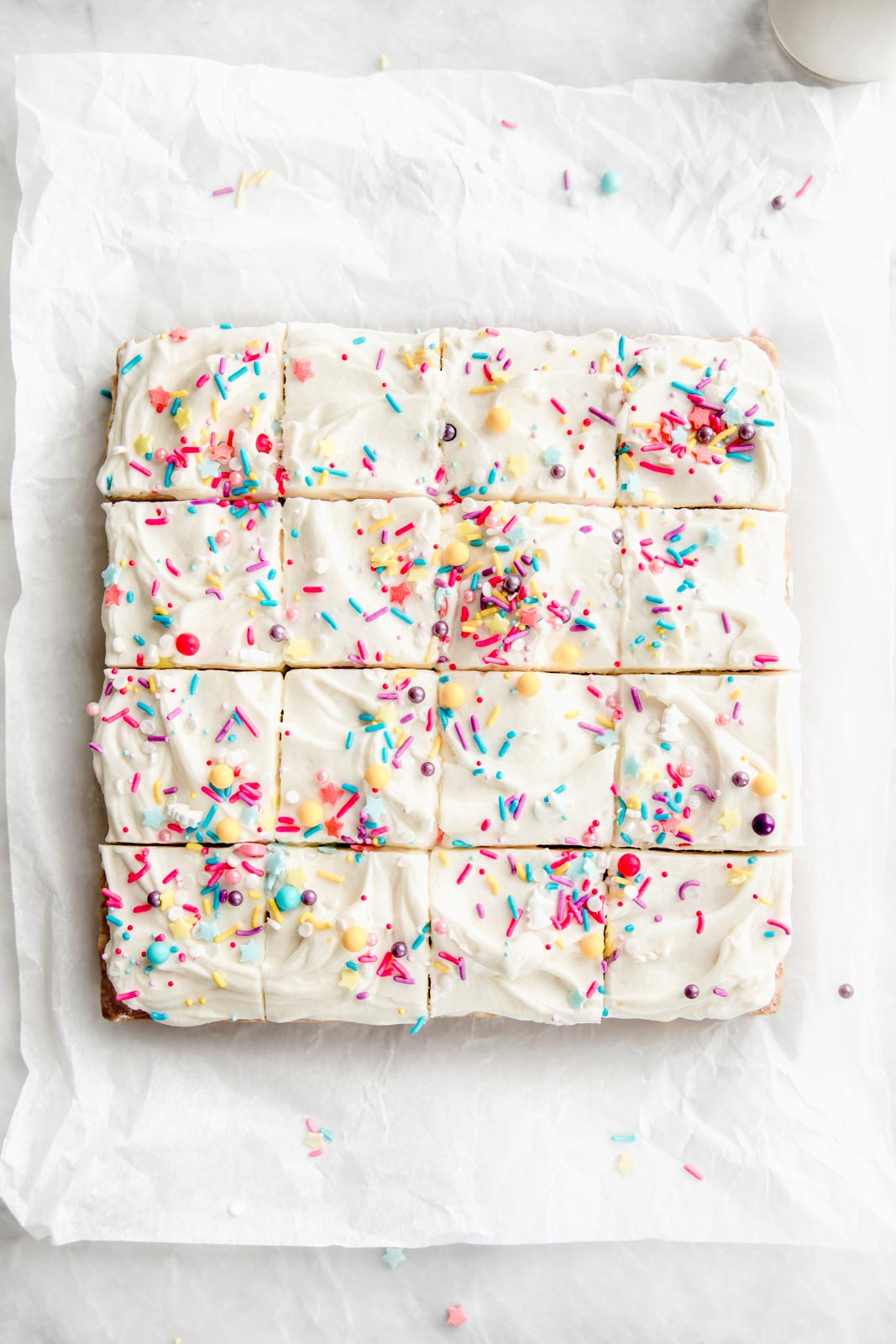 sugar cookie bars cut into squares with sprinkles on top