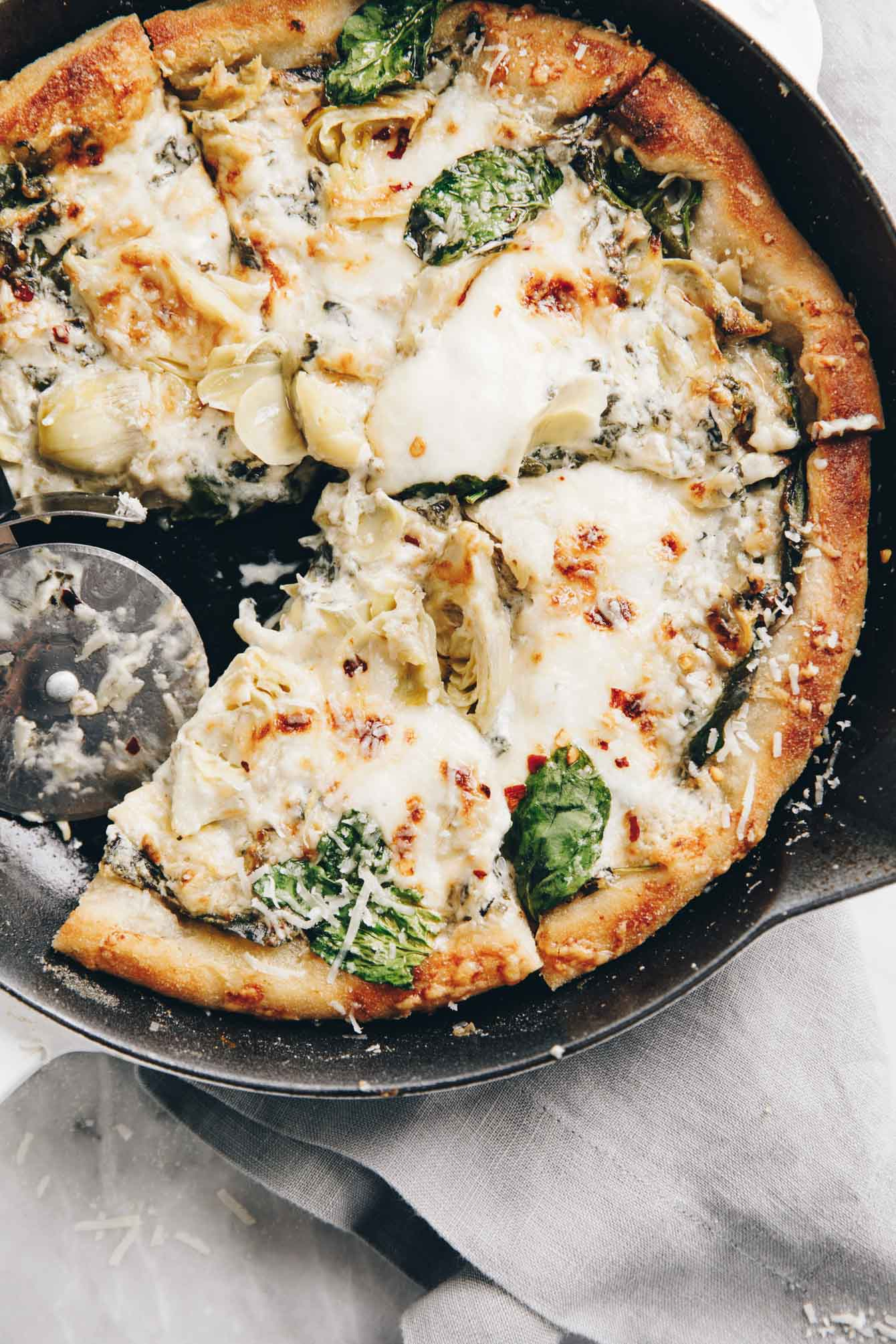 Easy cheesy spinach artichoke pizza so delicious, you'll eat the whole pie yourself
