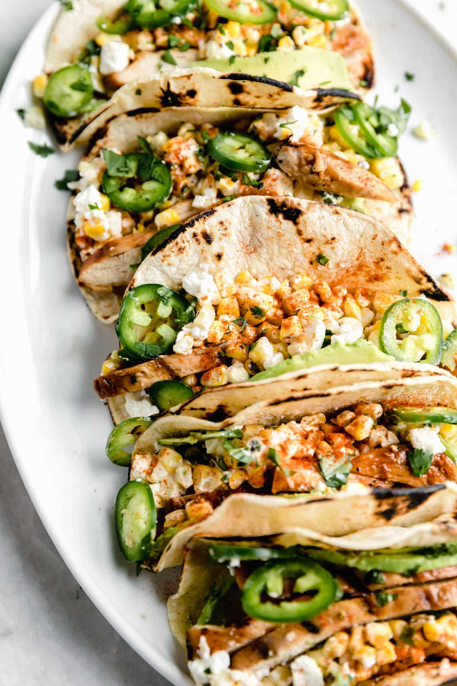 Kicking off Summer Taco Tuesdays with BBQ Chicken Mexican Street Corn tacos loaded with crema, cotija cheese, avocado, and fresh corn. Sign me up!