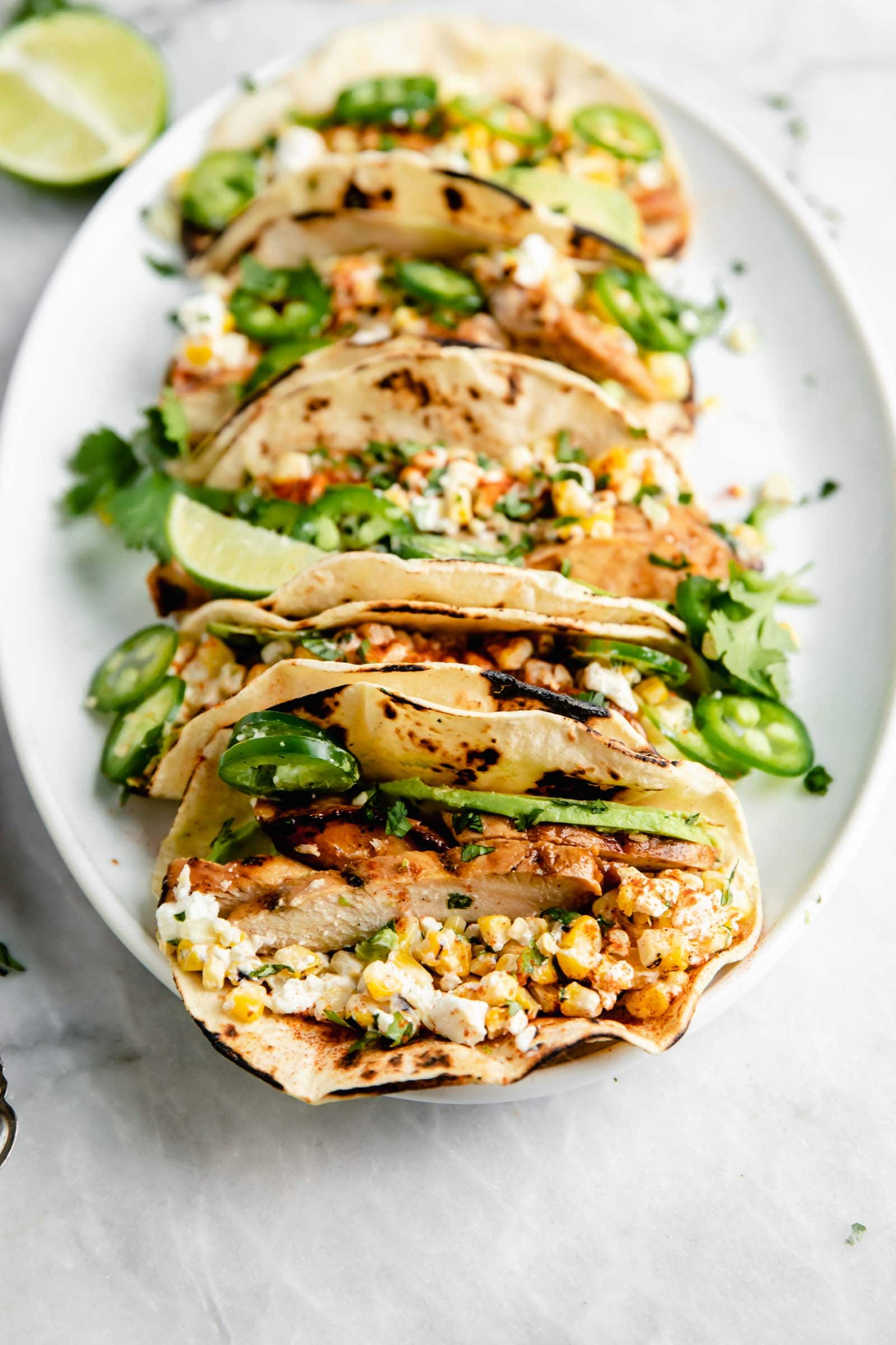 loaded barbecue chicken street corn tacos on a plate