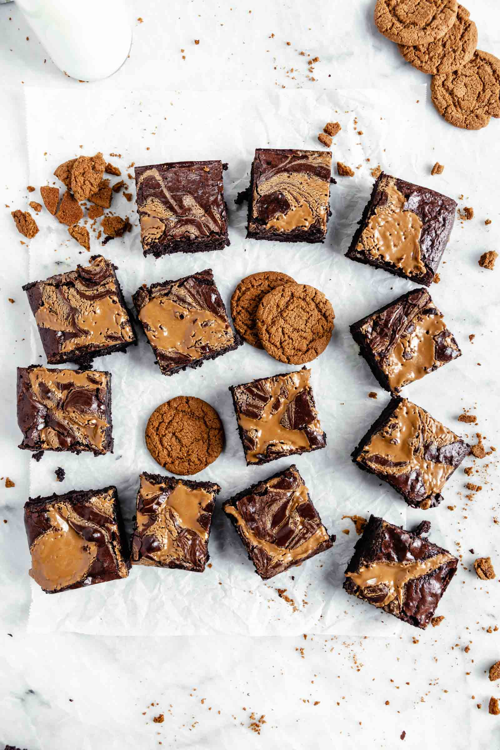cookie butter swirled brownies with crushed up cookies on marble board