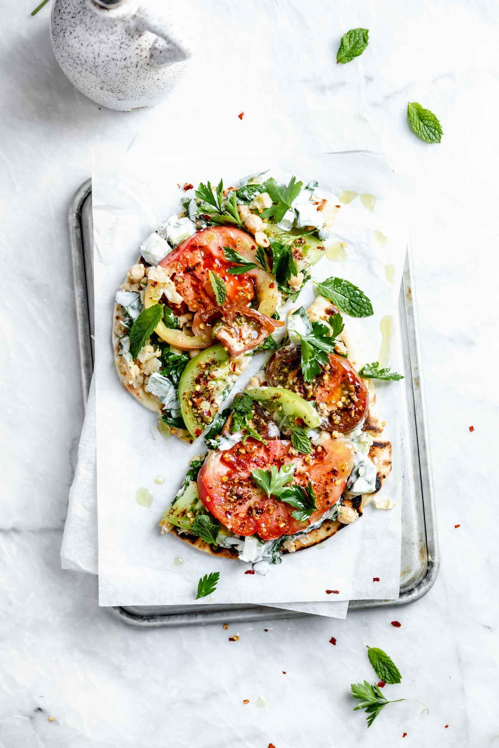 falafel-spice tomato flatbread cut in half on board