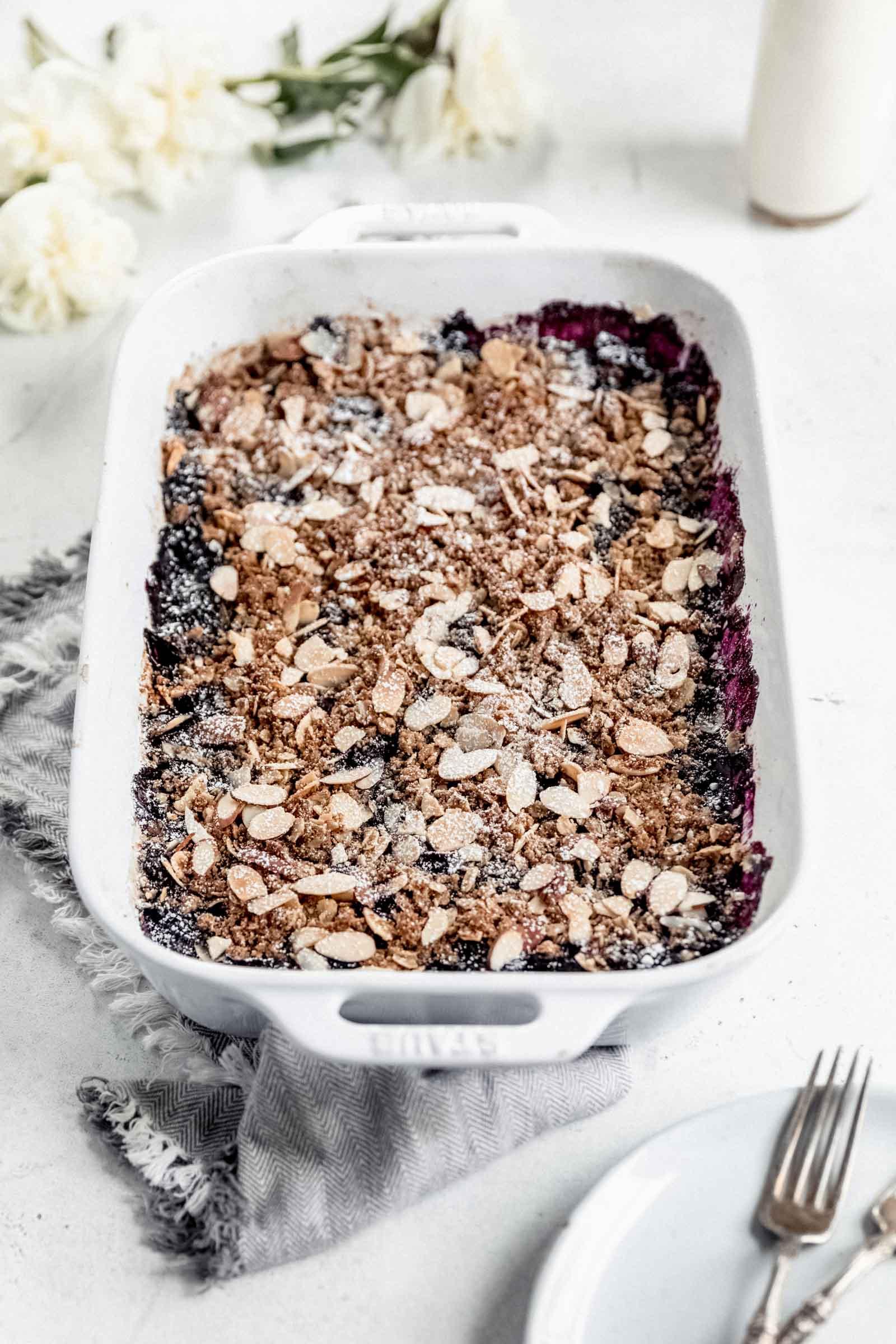 vegan blueberry crisp sprinkled with powdered sugar
