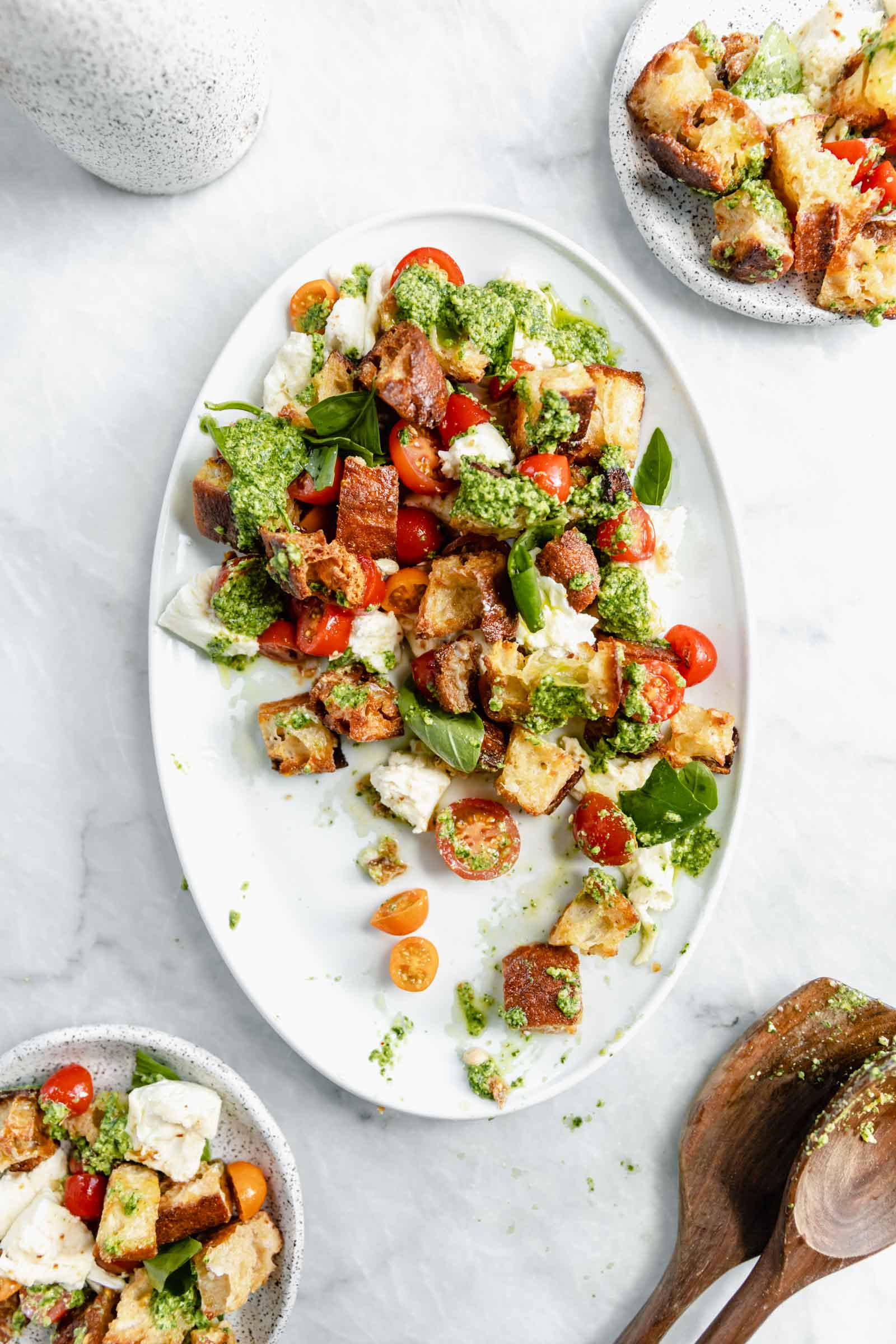 serving dish of panzanella salad with two smaller servings