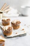 three apple carrot muffins with streusel and sliced apples on a cooling rack