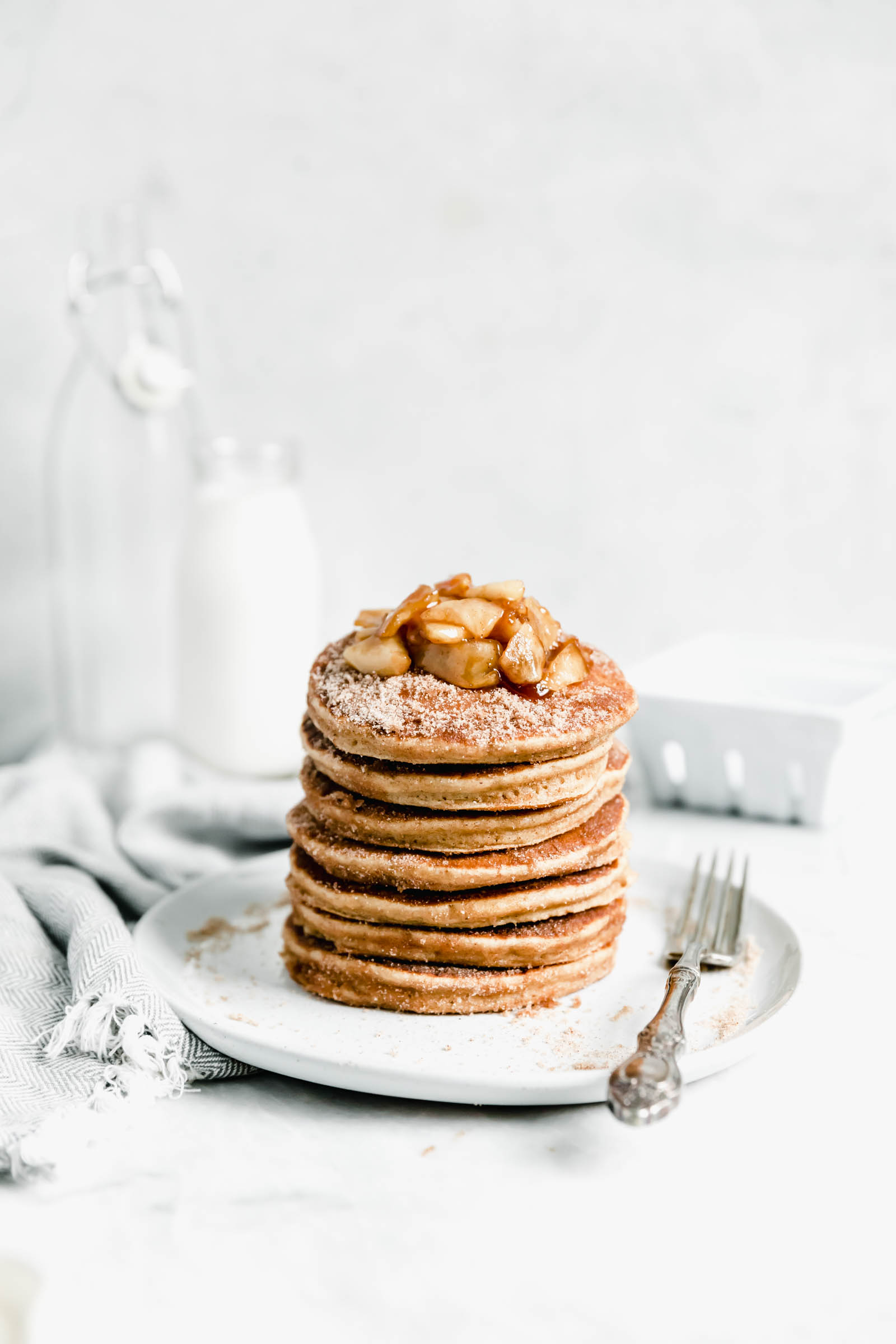 stack of apple pancakes covered in cinnamon sugar on a plate