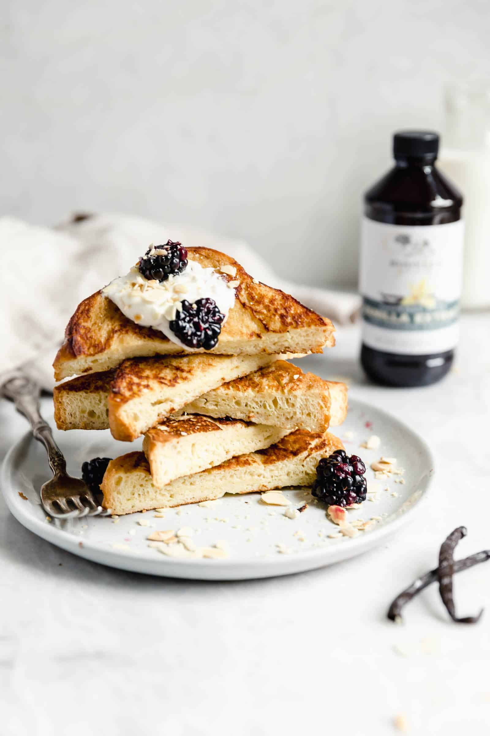 french toast cut into triangles topped with whipped cream and berries