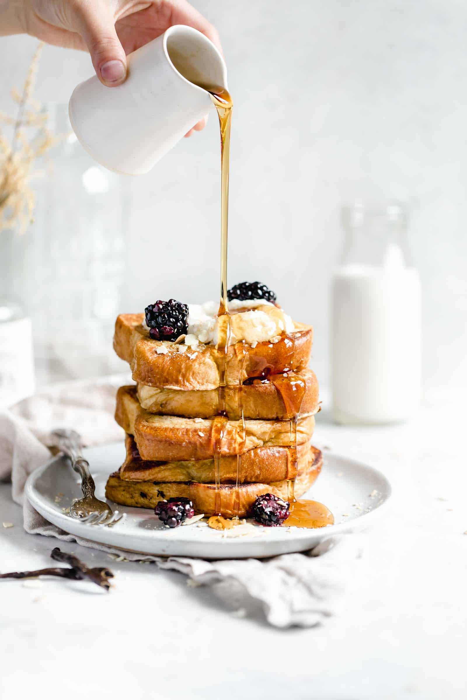 bourbon vanilla french toast stack with a generous pour of maple syrup