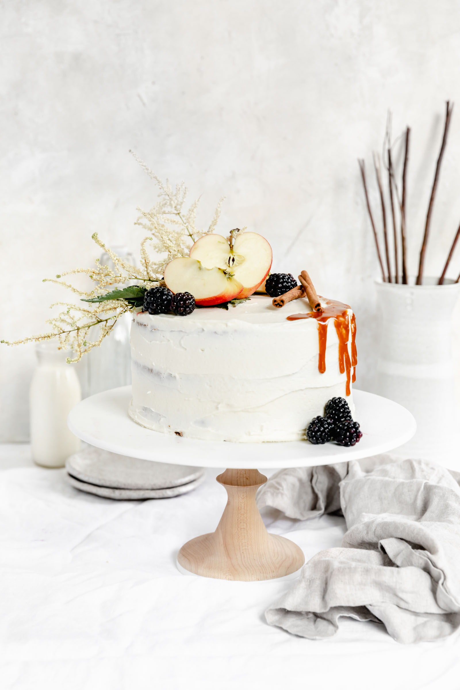 apple cake on cake stand topped with apples, berries and fall flowers