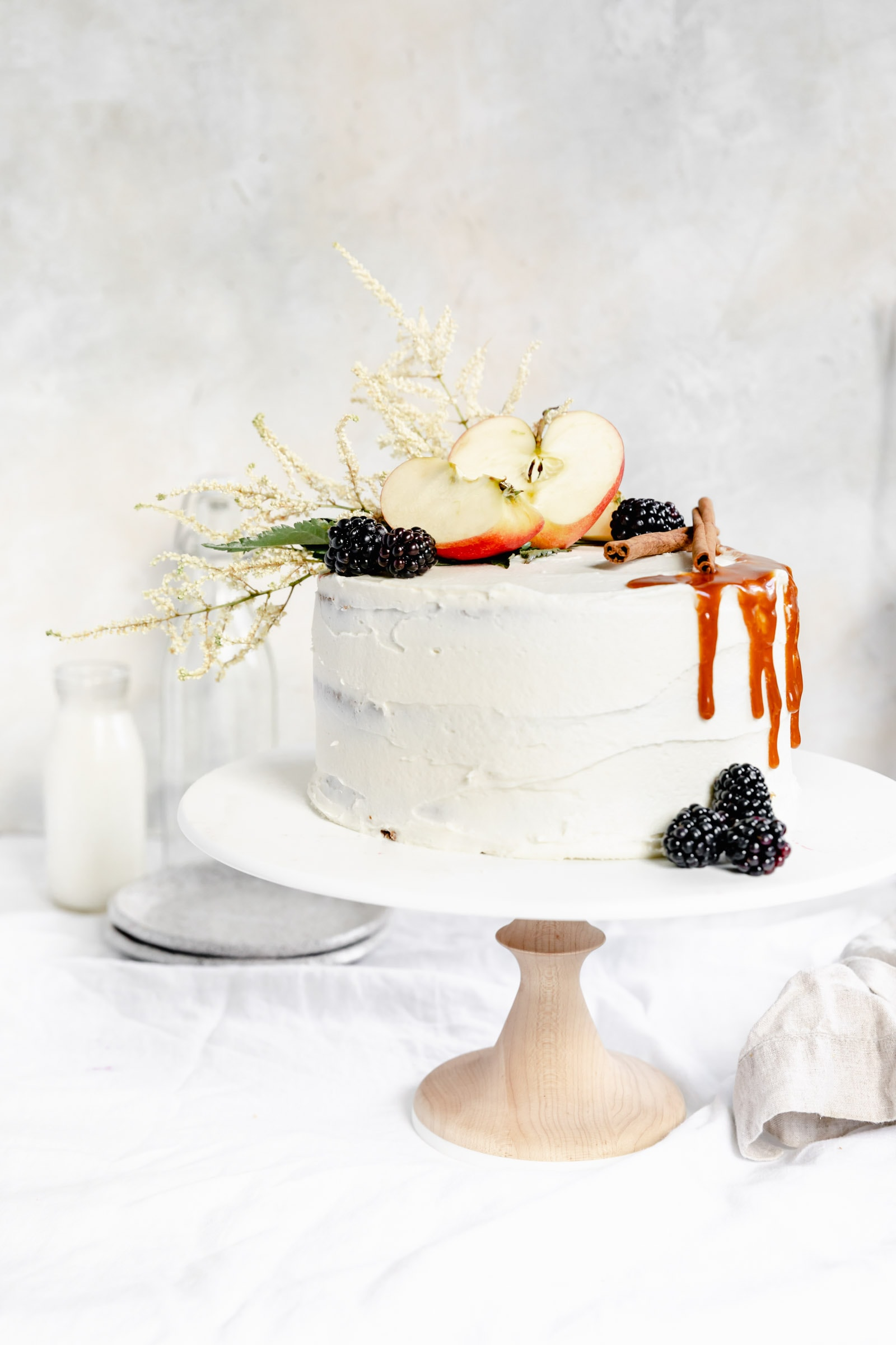 apple cake with cream cheese frosting and berries on a cake stand