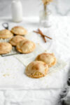 cinnamon apple hand pies on a cooling rack with two in the front on parchment paper