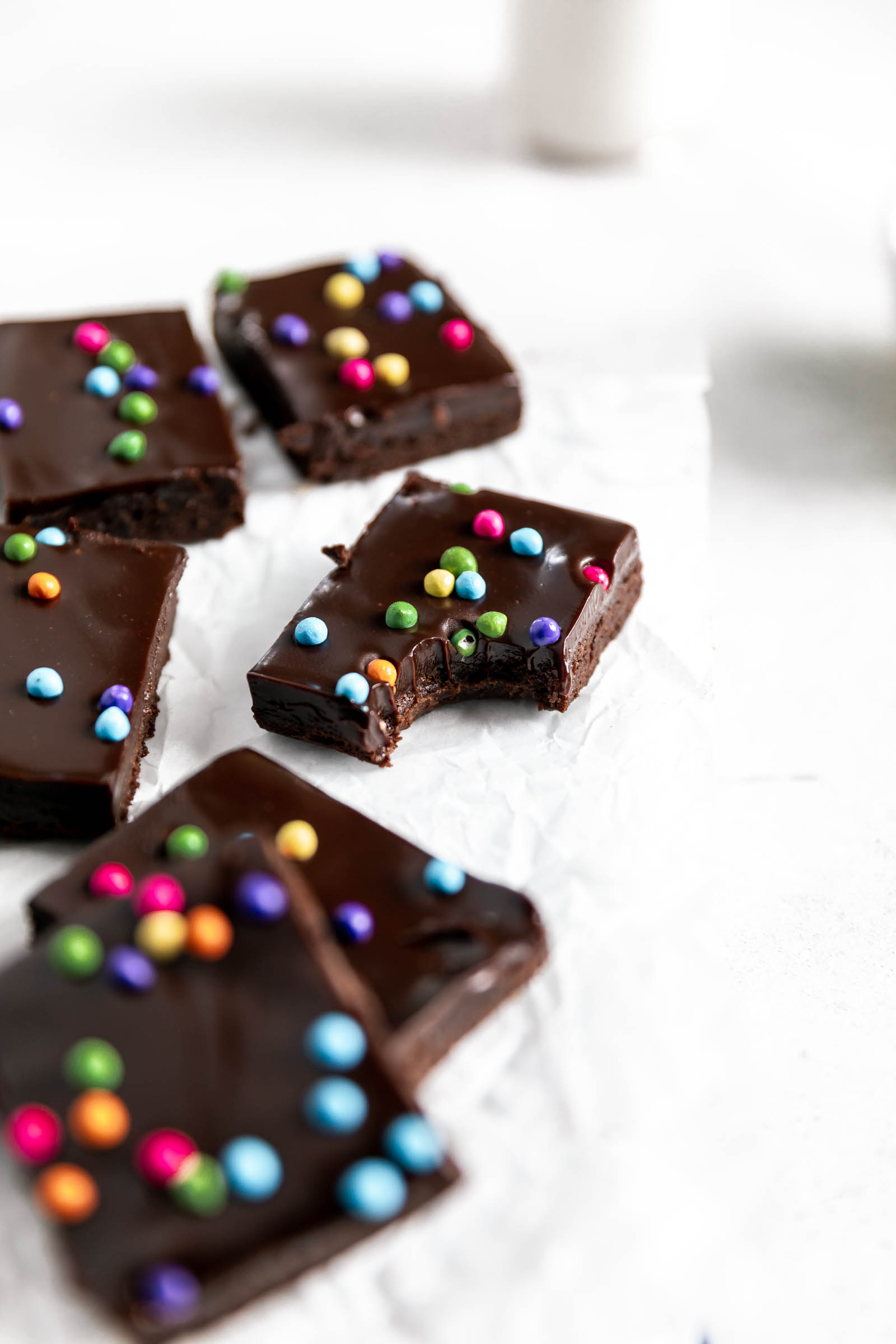 fudgy brownies with candy chocolate sprinkles and a bite taken out of it