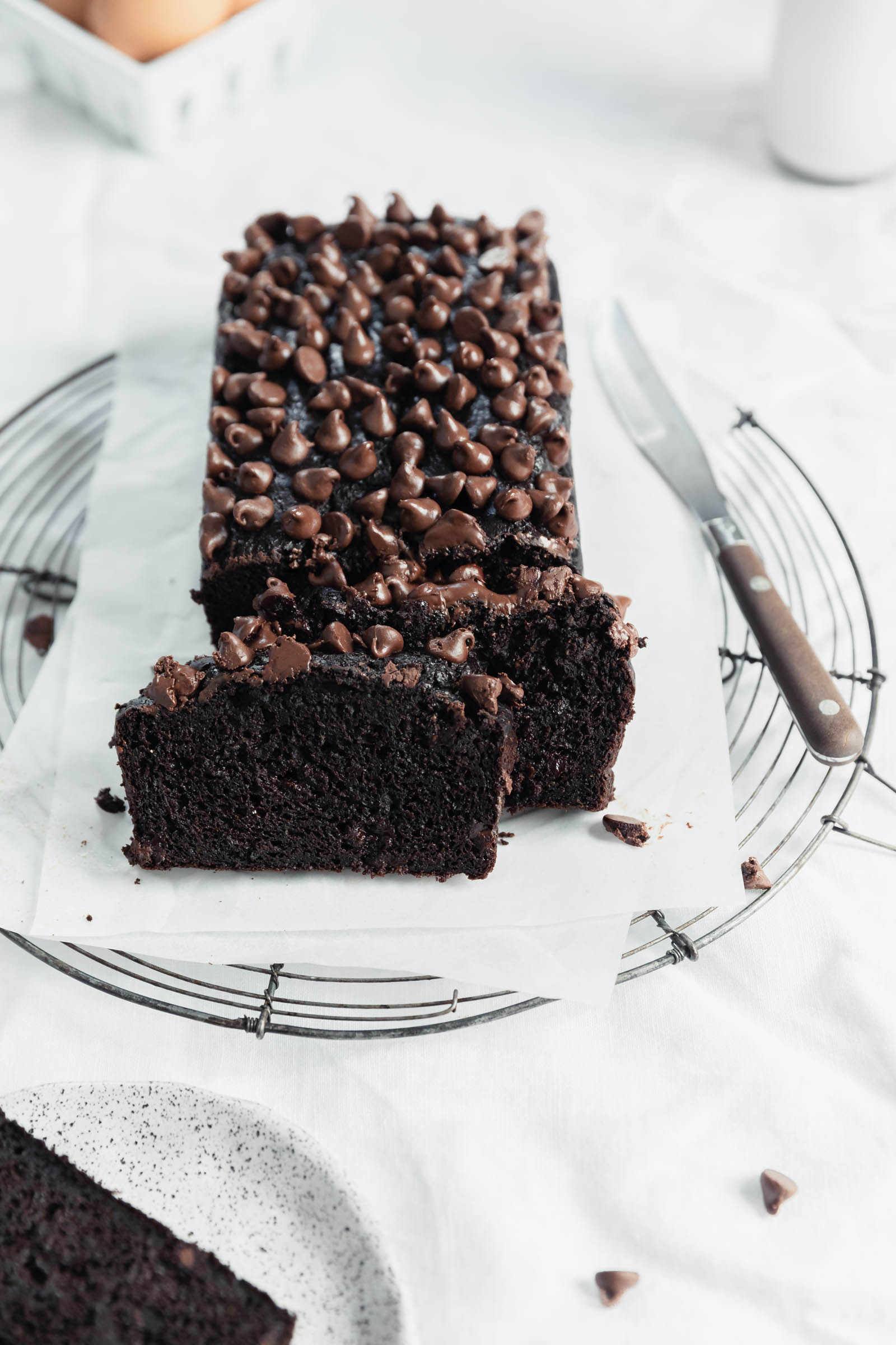 double chocolate zucchini bread with a slice and chocolate crumbs