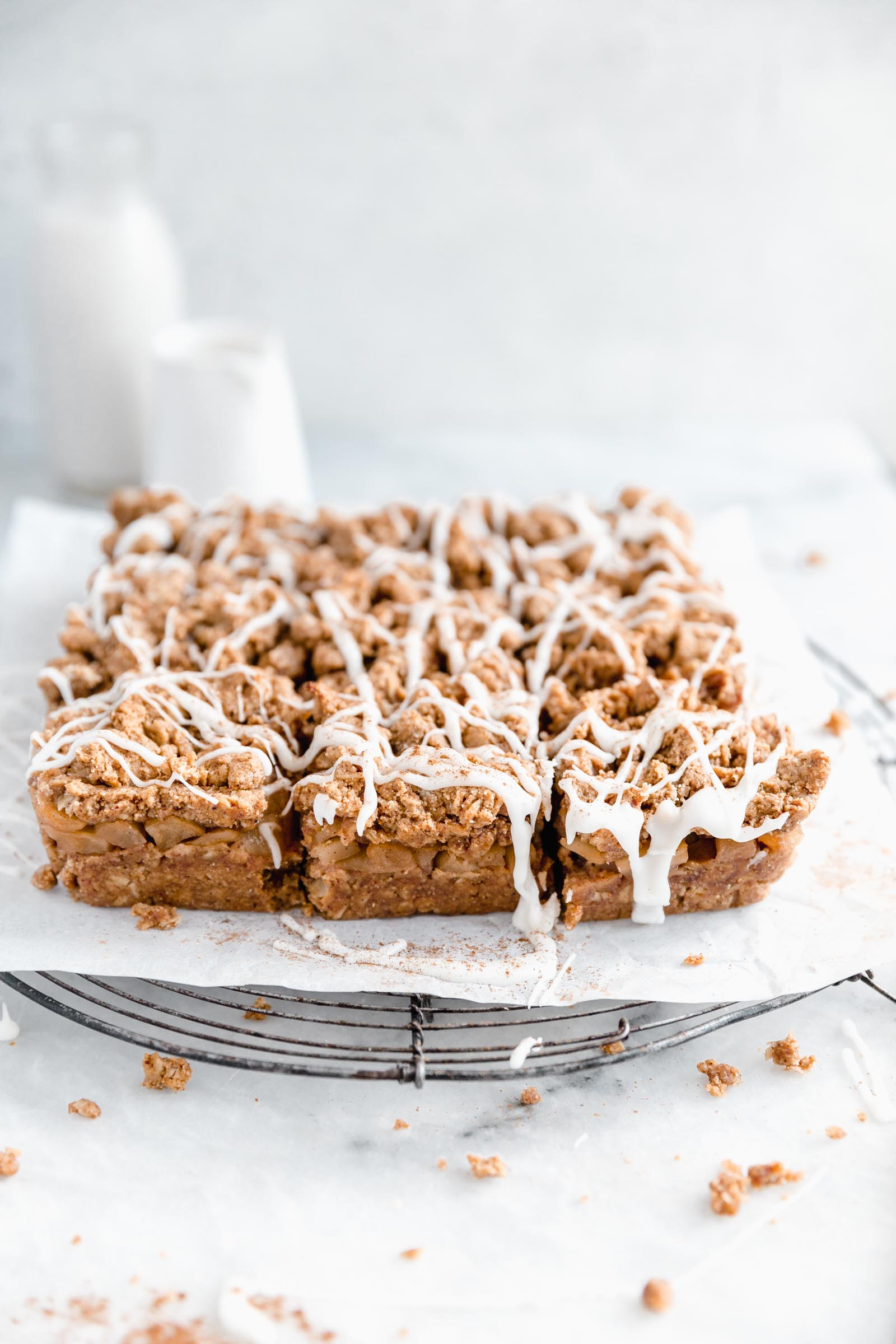 Apple crumble bars drizzled with icing on a cooling rack