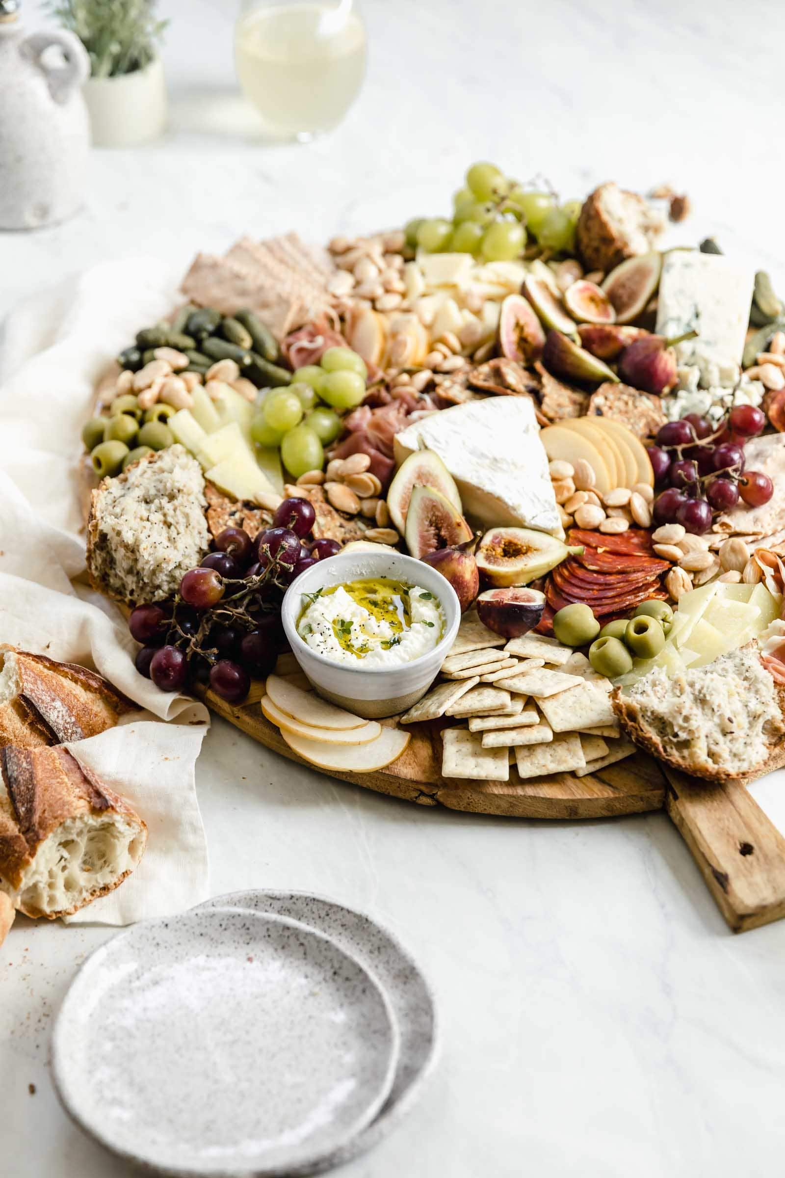 loaded cheeseboard on wooden board with wine