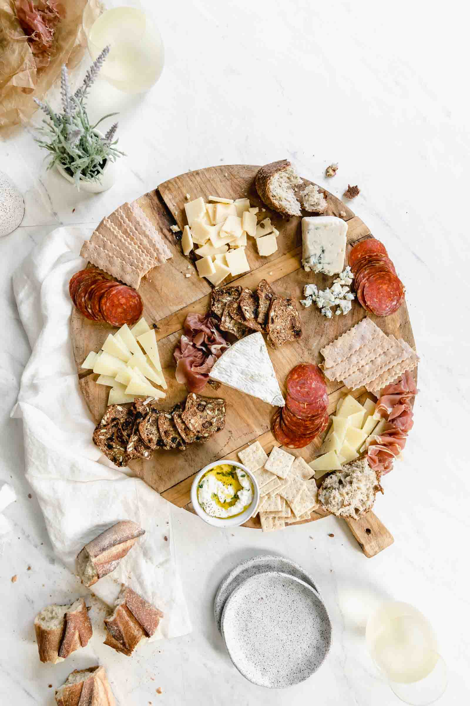 add variety of meats to cheese and and crackers on wooden board