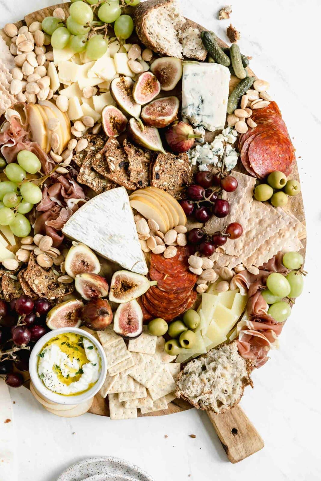 instagrammable cheeseboard loaded with cheese, meats, almonds, olives, and crackers
