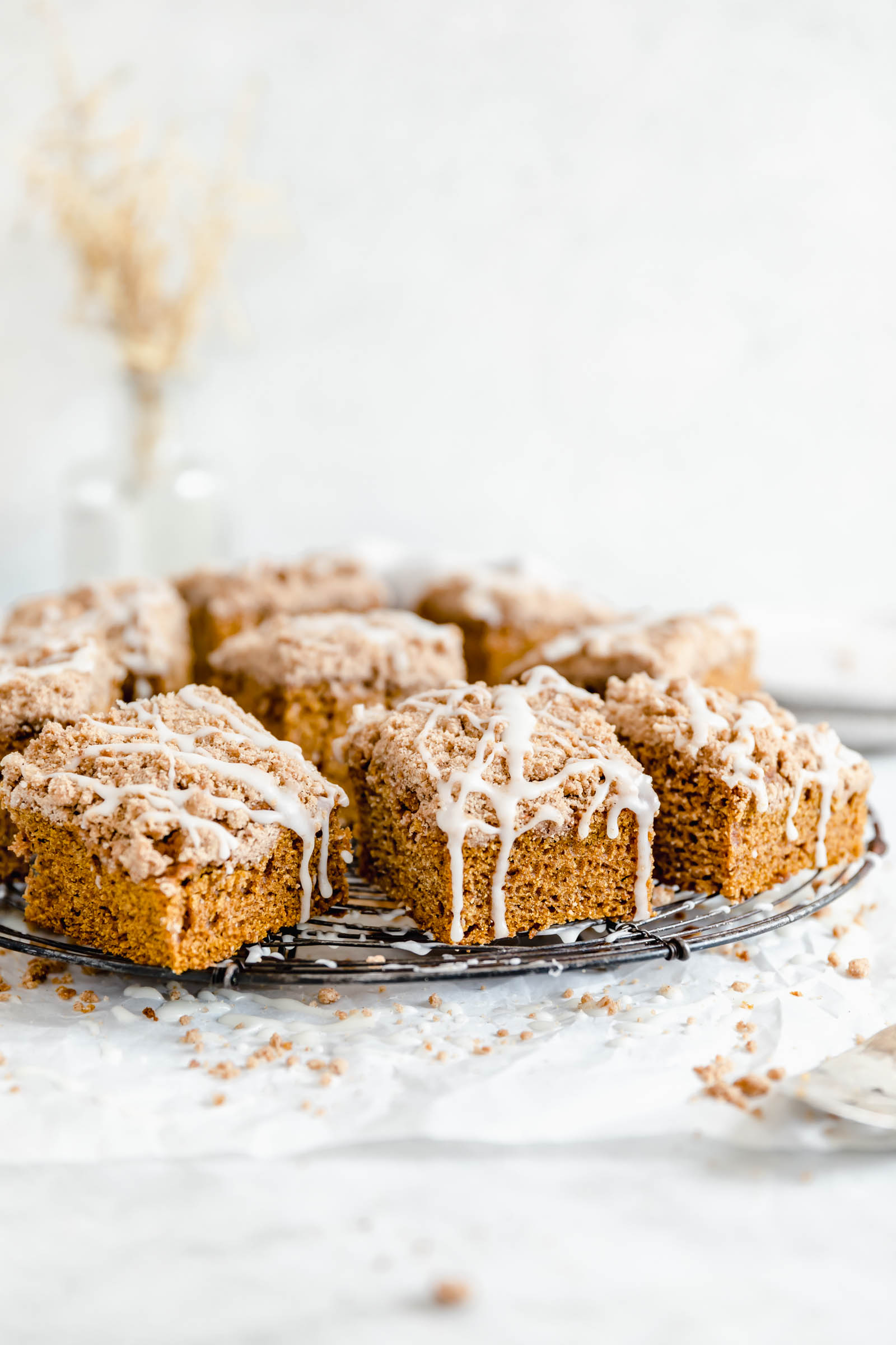 moist pumpkin coffee cake slices with glaze on a circular cooling rack