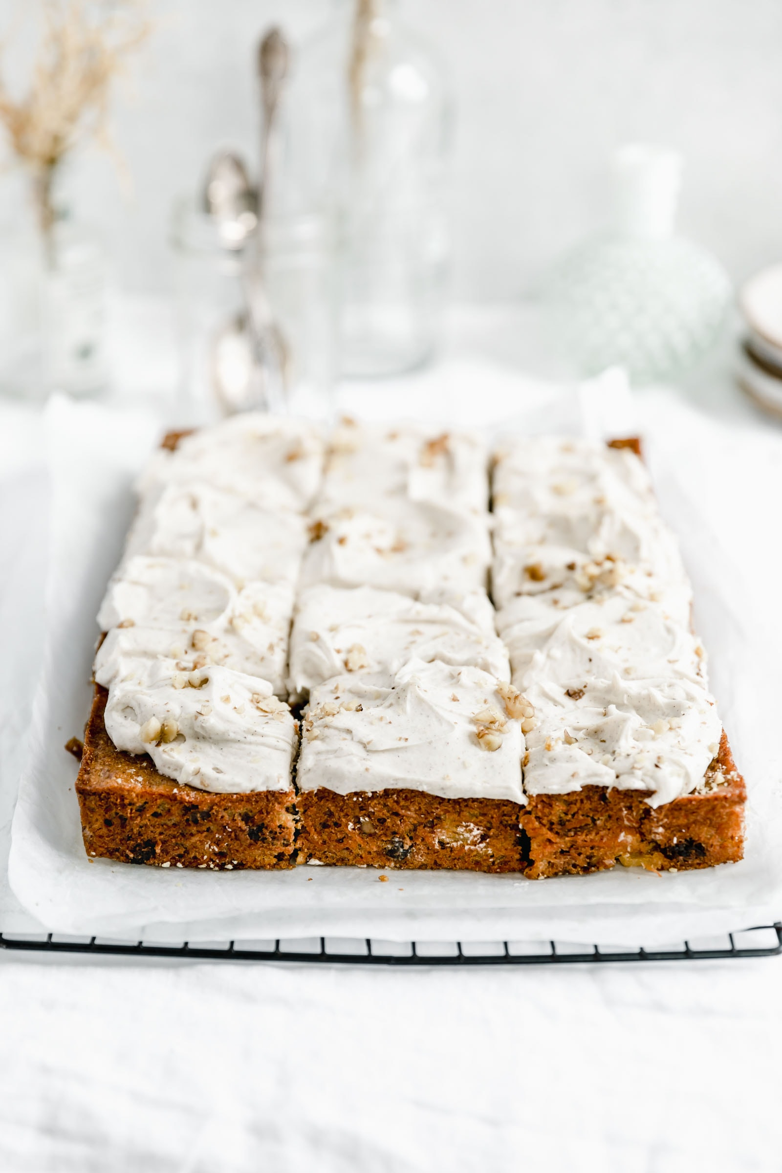 carrot sheet cake with a thick layer of cream cheese frosting cut into 12 pieces