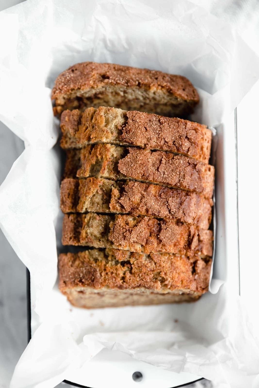 overhead shot of snickerdoodle banana bread in white loaf pan with parchment paper