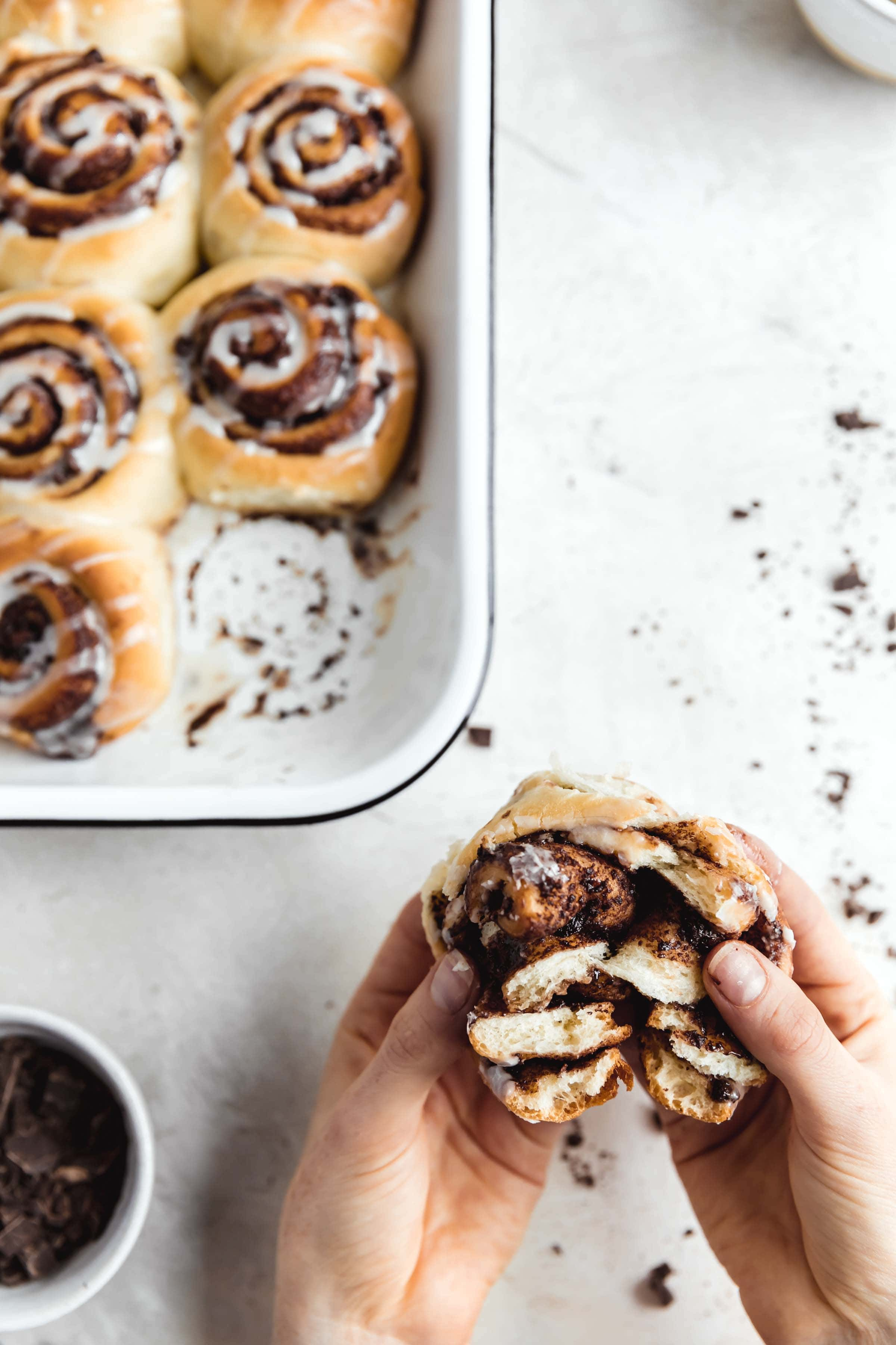 decadent 1 hour chocolate cinnamon rolls in a pan with the gooiest center and a cream cheese icing drizzle