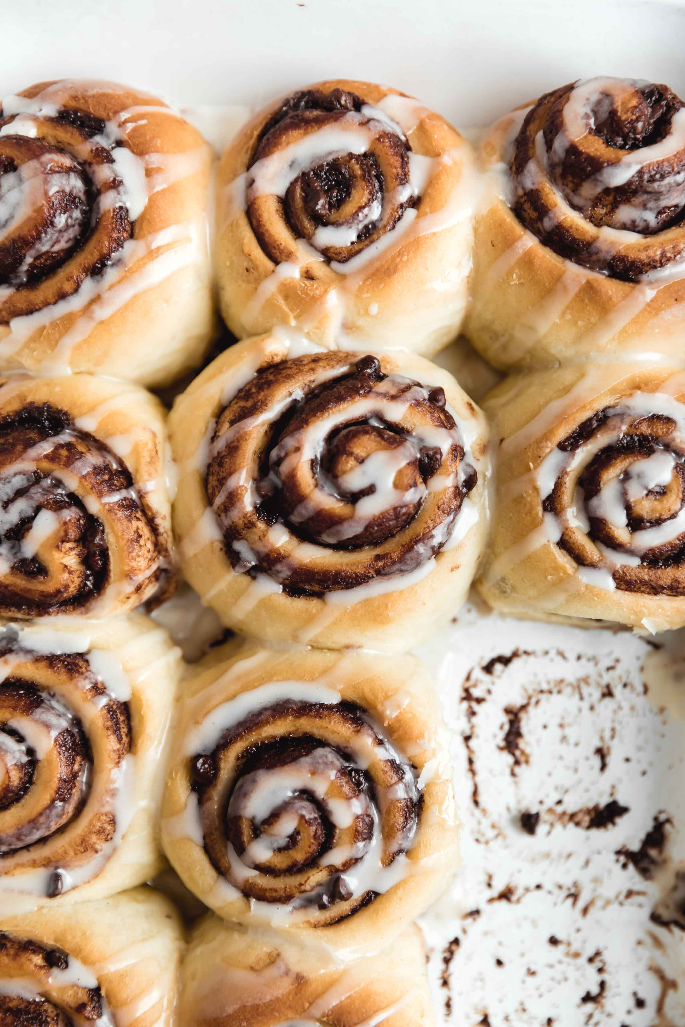 Nothing says holiday baking more than cinnamon rolls...except maybe CHOCOLATE cinnamon rolls. These pillow soft cinnamon rolls are filled with chocolate, drizzled wit the most perfect cream cheese icing and absolutely scrumptious. Best part? They're ready in under an hour. #cinnamonrolls #bromabakery #foodphotography #easy
