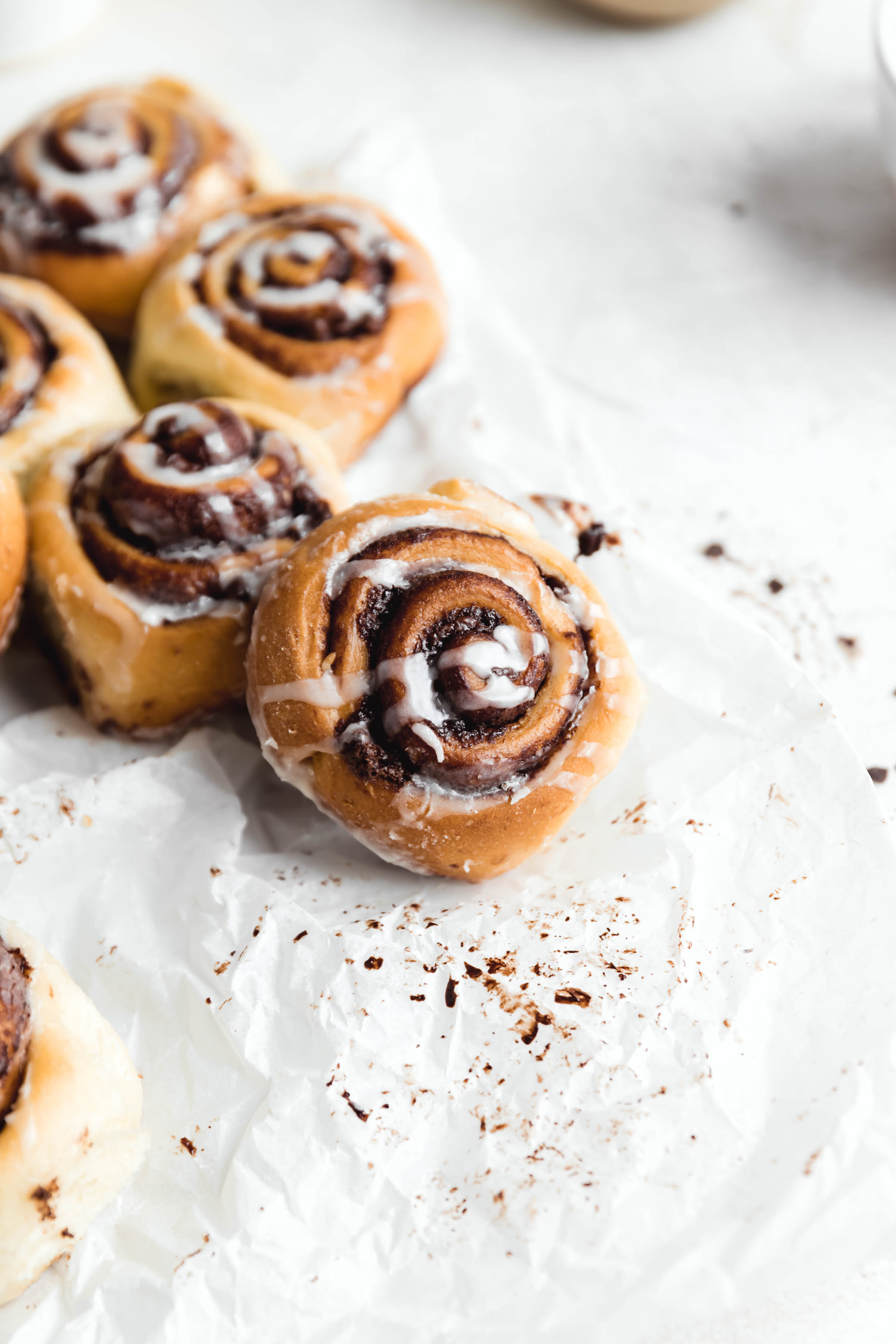 chocolate cinnamon rolls drizzled with cream cheese icing