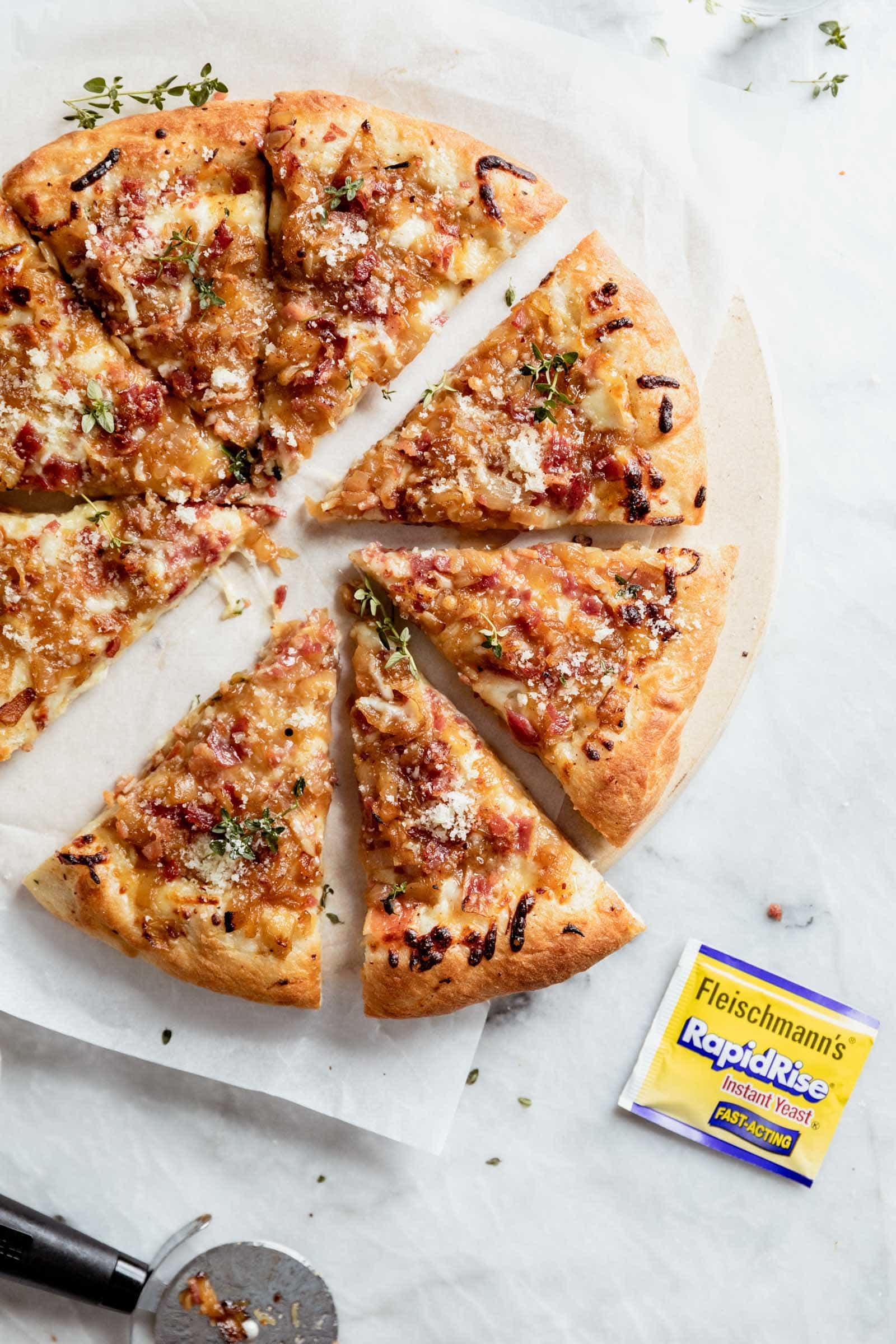 caramelized onion bacon and gruyere pizza with pizza cutter and rapid rise yeast