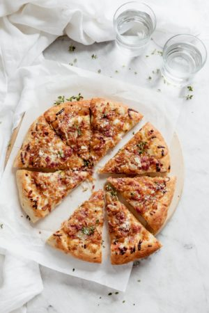 caramelized onion bacon and gruyere pizza pie cut into triangles