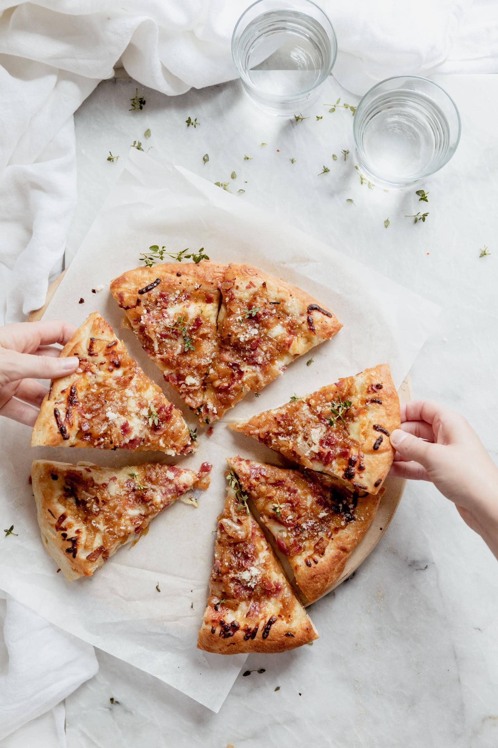 hands grabbing for caramelized onion bacon and gruyere pizza