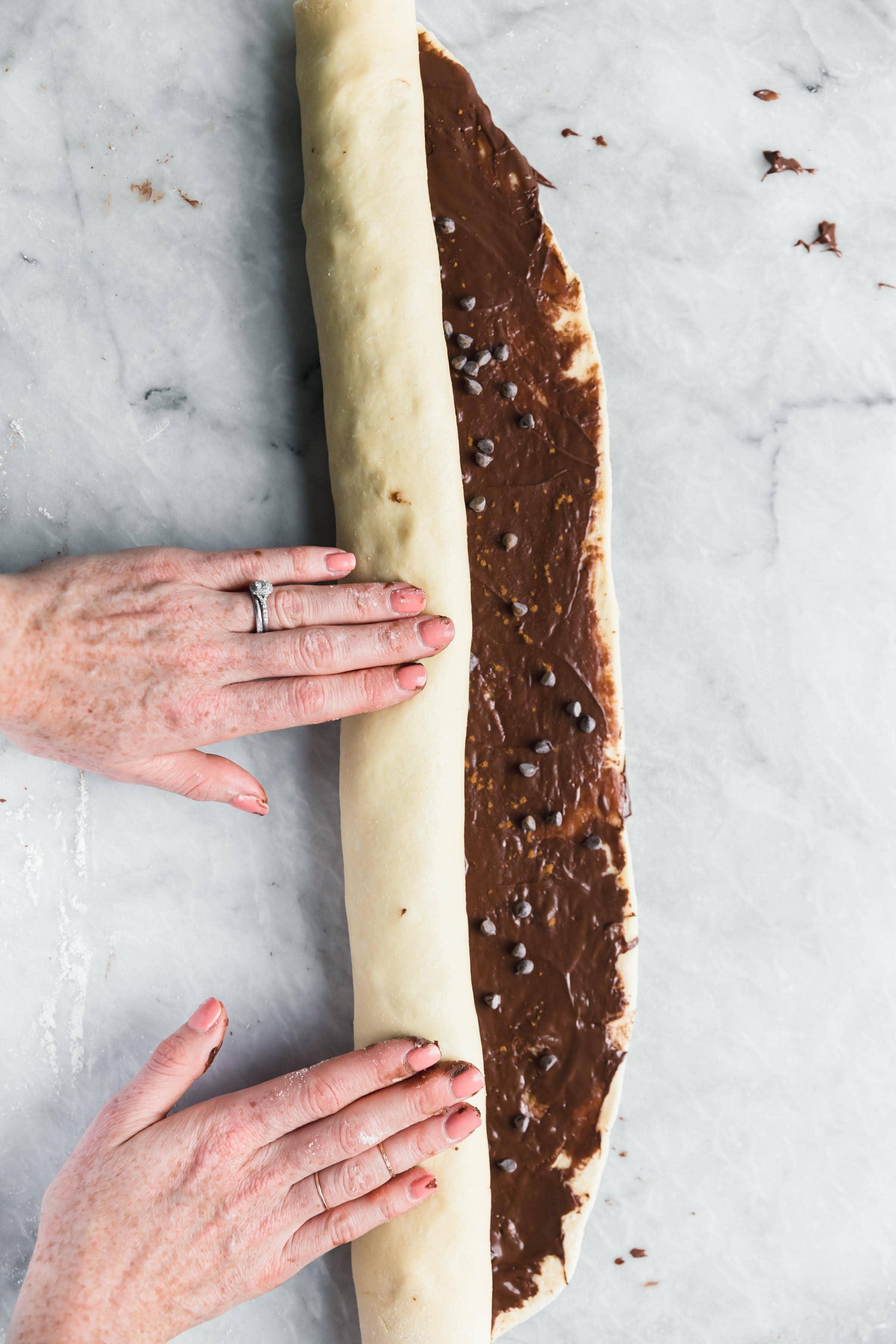 roll the cinnamon roll dough into a tight log