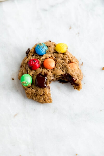 Bite shot of healthyish mosnter cookies studded with m and ms and dark chocolate chips