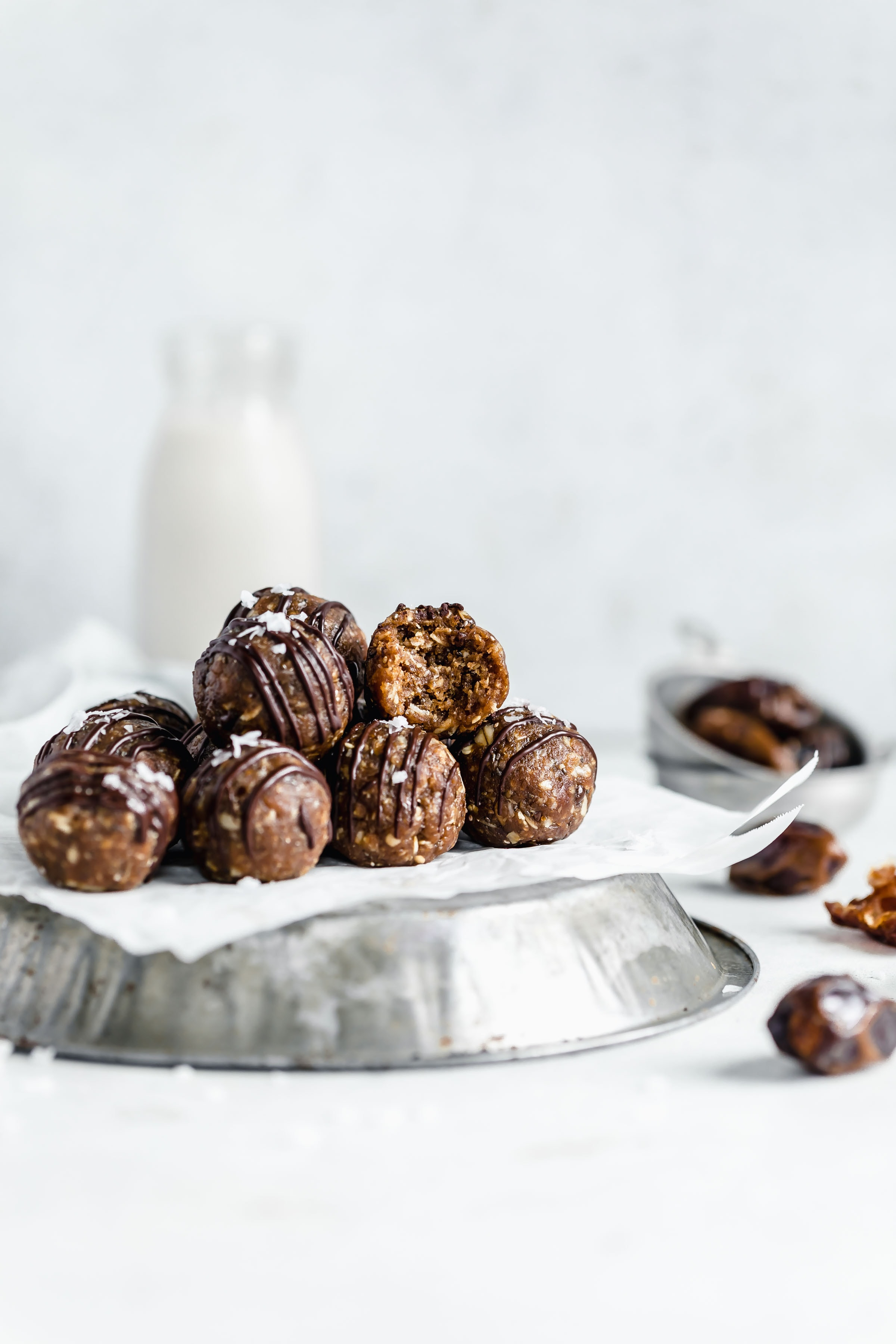 pile of peanut butter oat energy balls drizzled with chocolate on a pine tin with milk