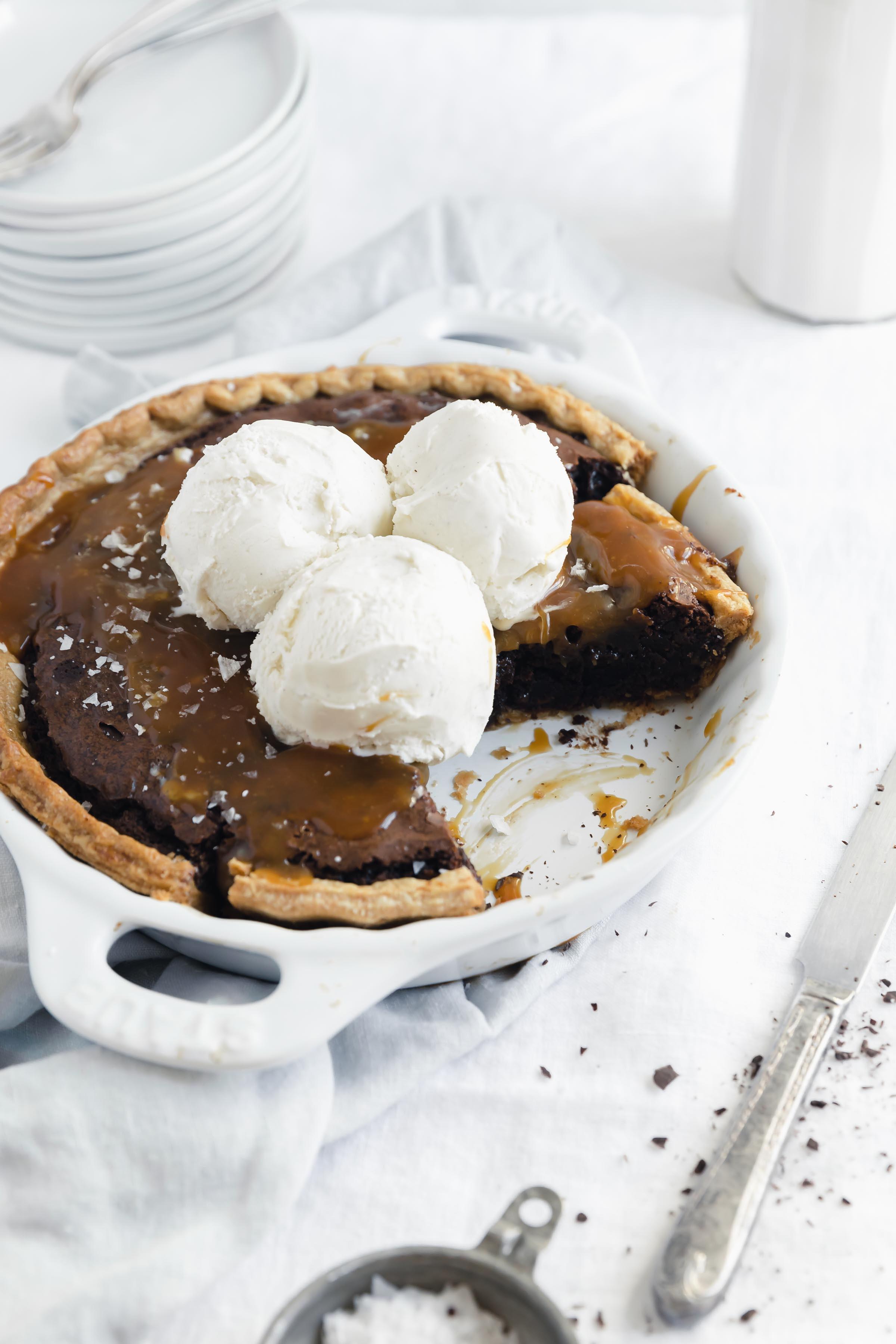 45 degree angle shot of easy salted caramel brownie pie in a white dish with a slice taken out