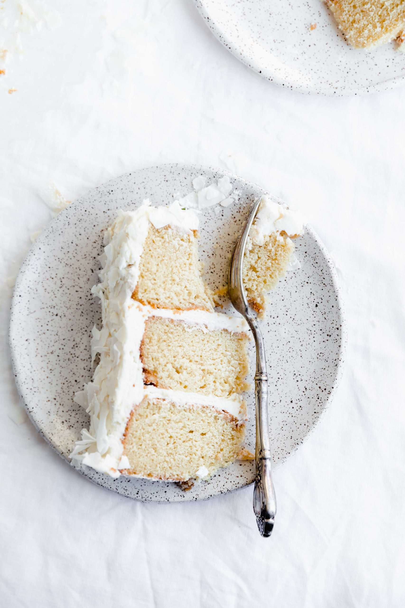overhead shot of piece of coconut layer cake