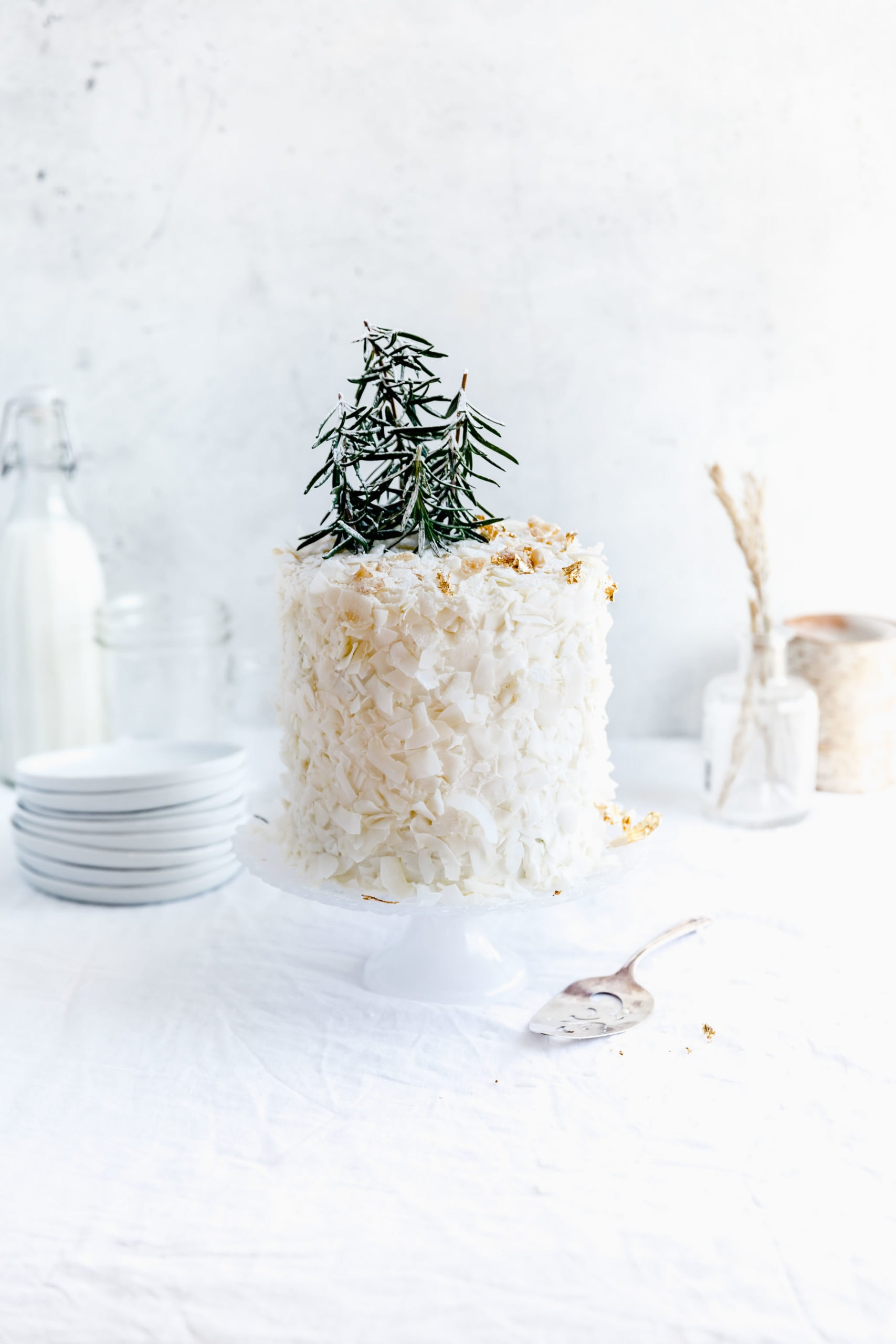 straight on shot of coconut layer cake on a cake stand