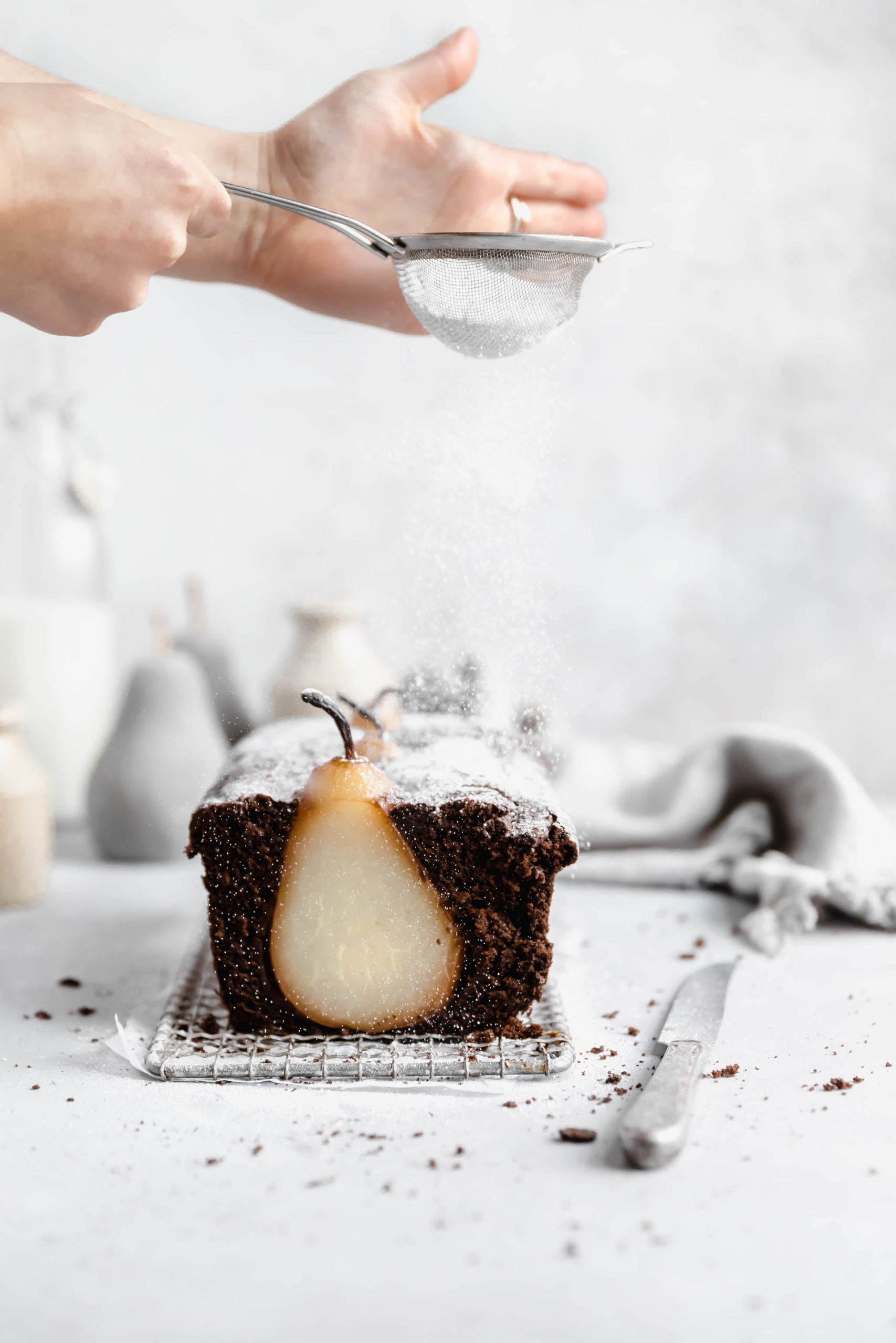poached pear gingerbread loaf cake with powdered sugar sprinkled on topr