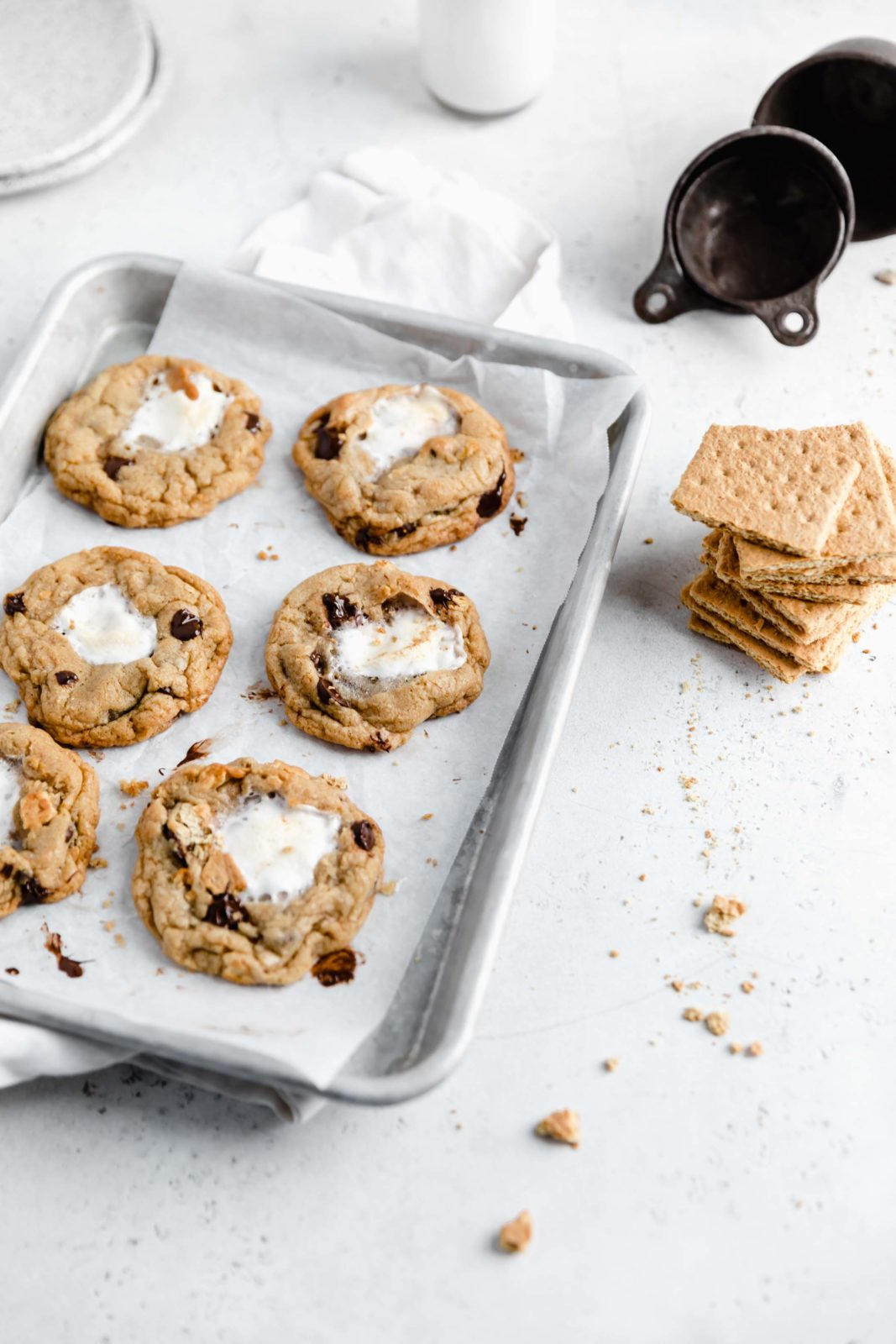 browned butter chocolate chip cookies stuffed with marshmallows and graham crackers on a cookie sheet
