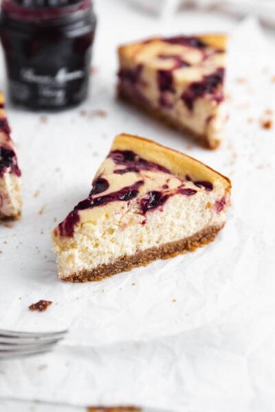 slice of healthy cherry cheesecake with big swirls of cherry jam and a graham cracker crust