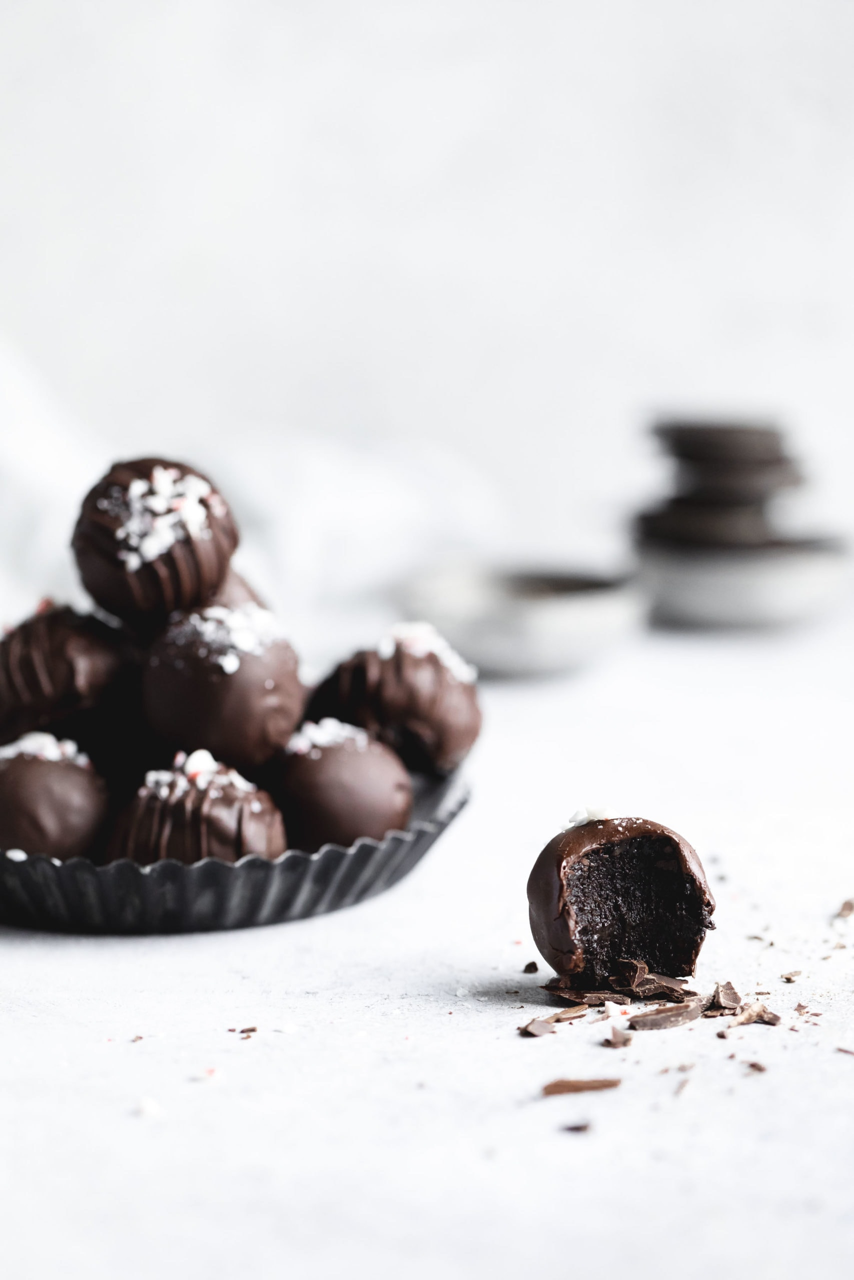 straight on shot of peppermint oreo truffles with one oreo truffle with a bite out of it