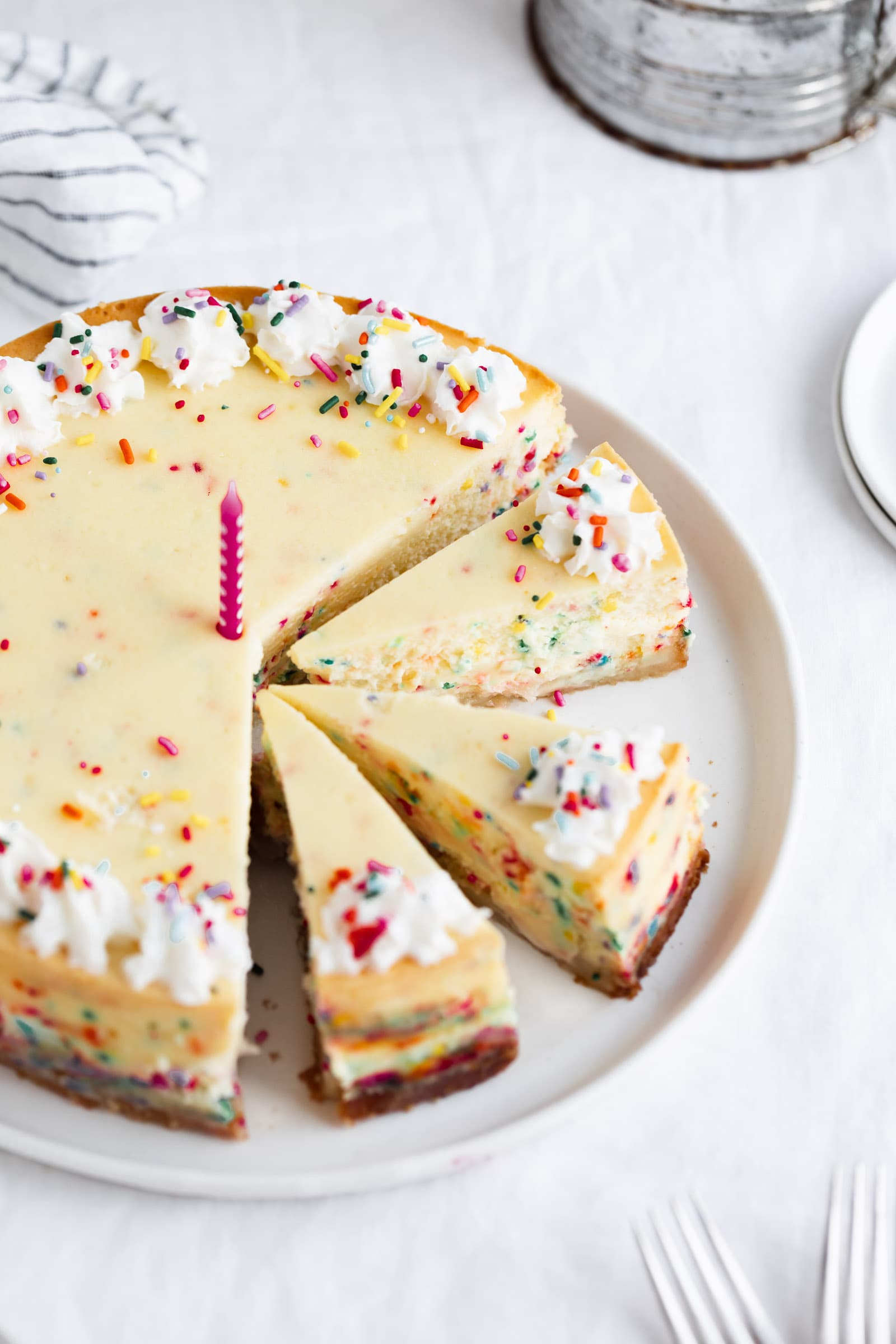 easy birthday cake cheesecake cut into pieces