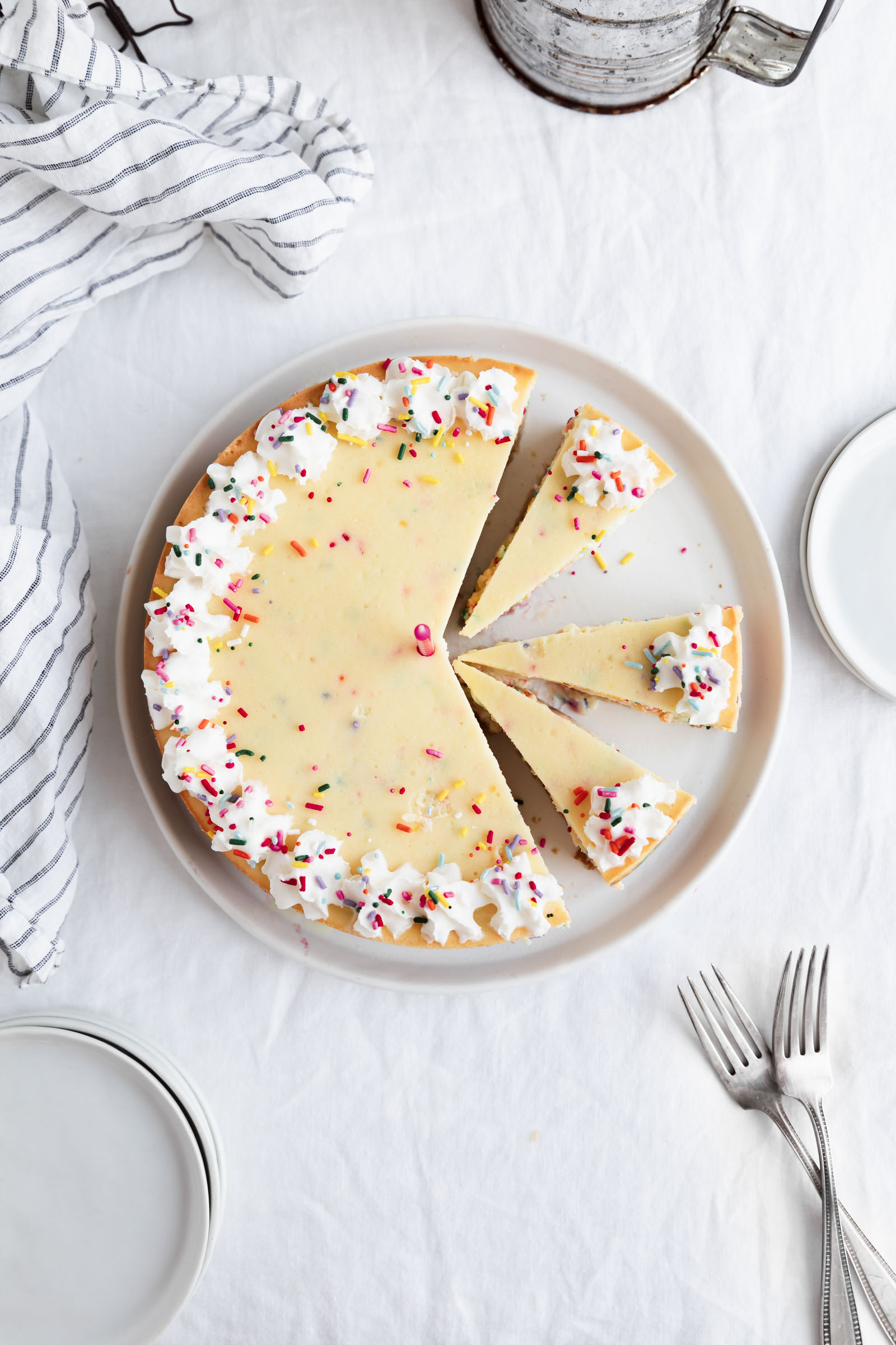 full birthday cheesecake with sprinkles and whipped cream