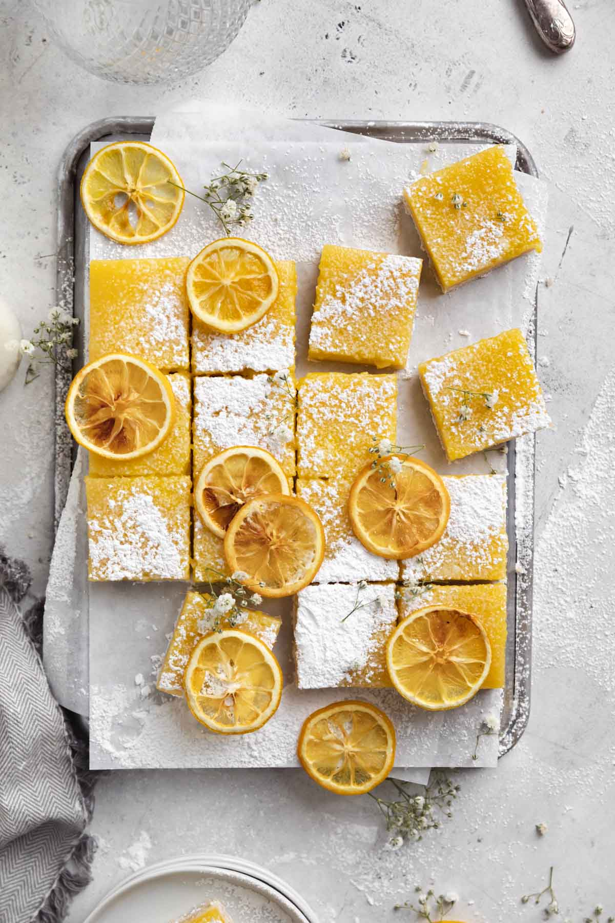 lemon bars dusted with powdered sugar on a cookie sheet